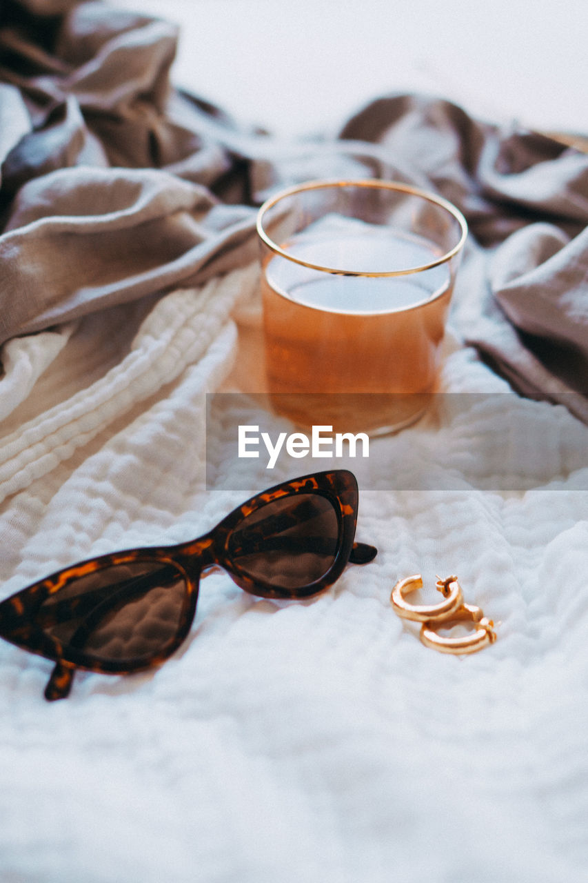 High Angle View Of Earrings And Sunglasses With Drink On Bed