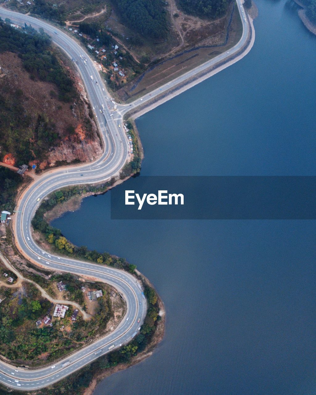 aerial view, road, curve, outdoors, winding road, day, transportation, landscape, high angle view, water, no people, mountain, mountain road, tree, scenics, nature, beauty in nature, sky