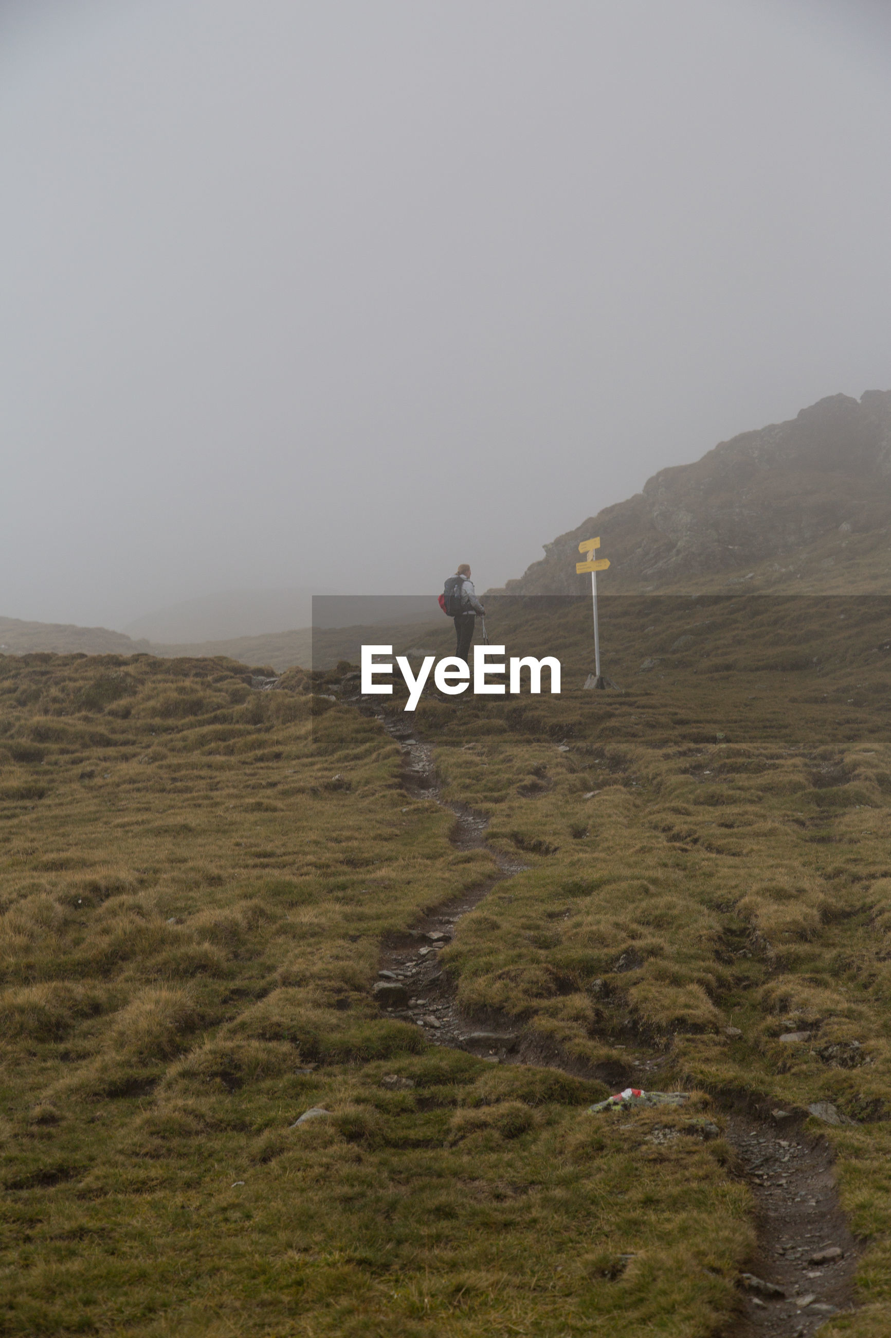 Male hiker with backpack standing on field during foggy weather