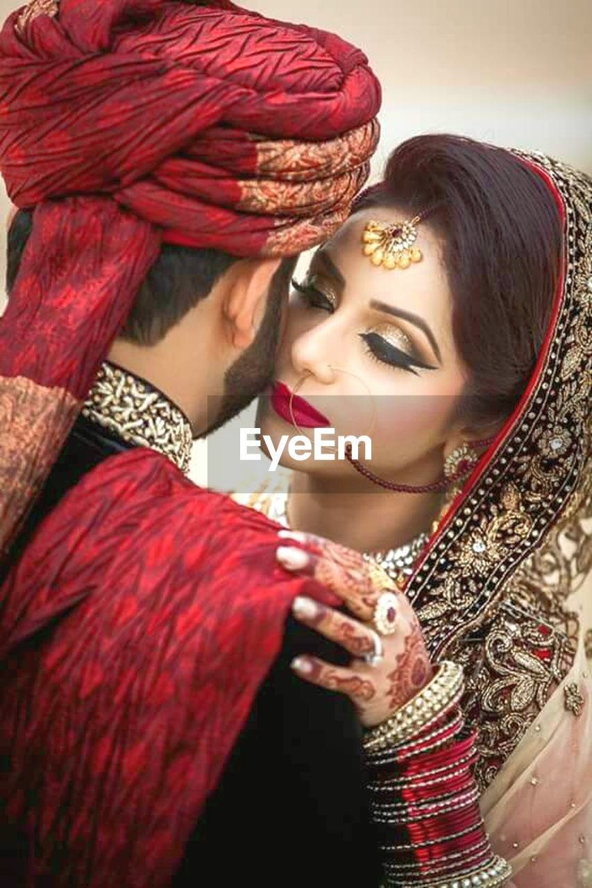 red, young women, jewelry, young adult, beauty, traditional clothing, beautiful people, fashion, adult, only women, females, adults only, beautiful woman, make-up, women, portrait, gold colored, smiling, real people, celebration, people, glamour, turban, ceremony, veil, sari, gold, one young woman only, stage costume, bride, close-up, period costume, day