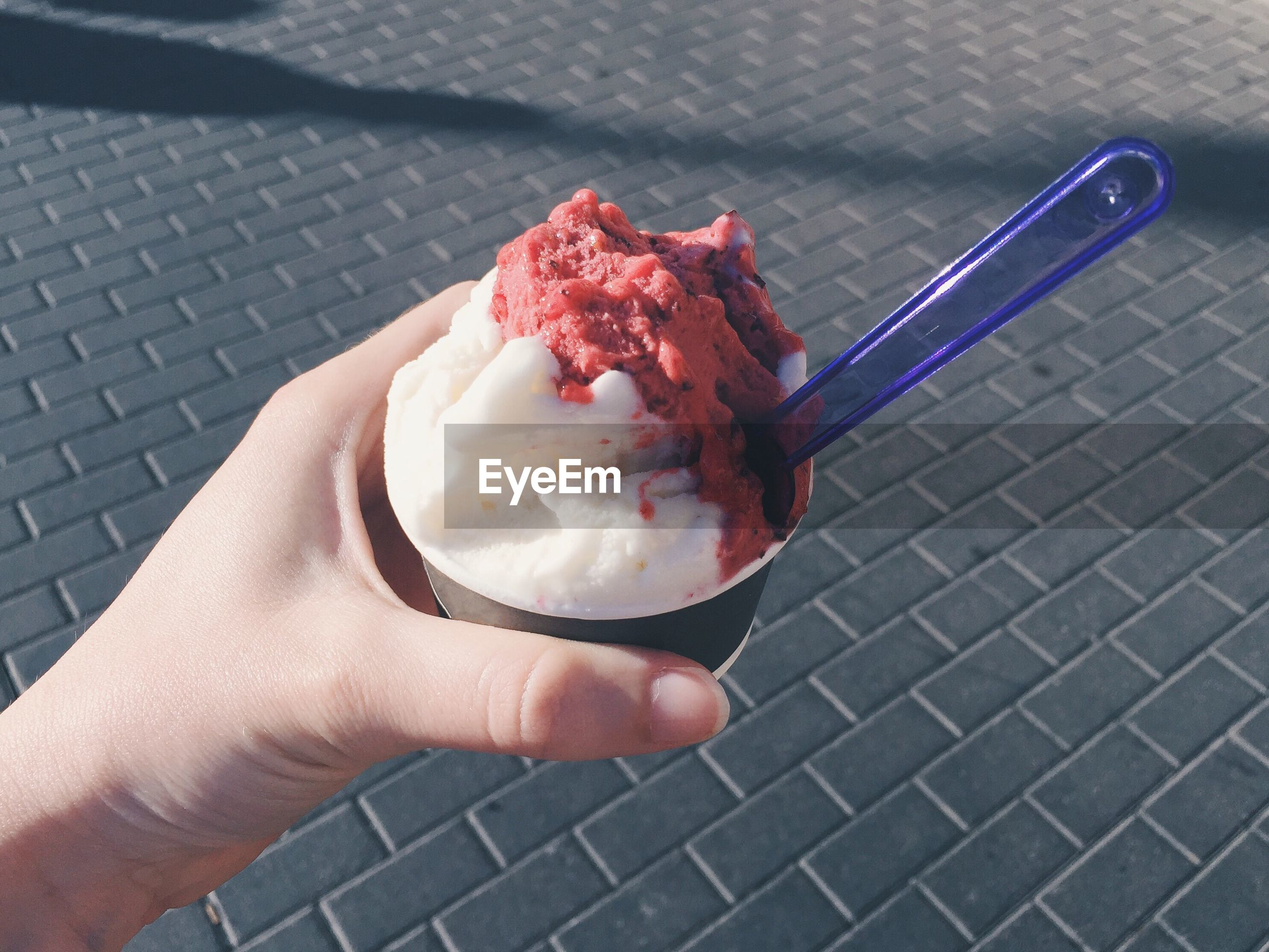 Cropped hand of woman holding ice cream cup against footpath in city during summer