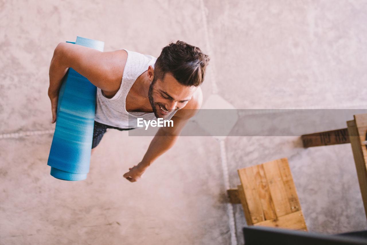 Full Length Of Man Carrying Yoga Mat
