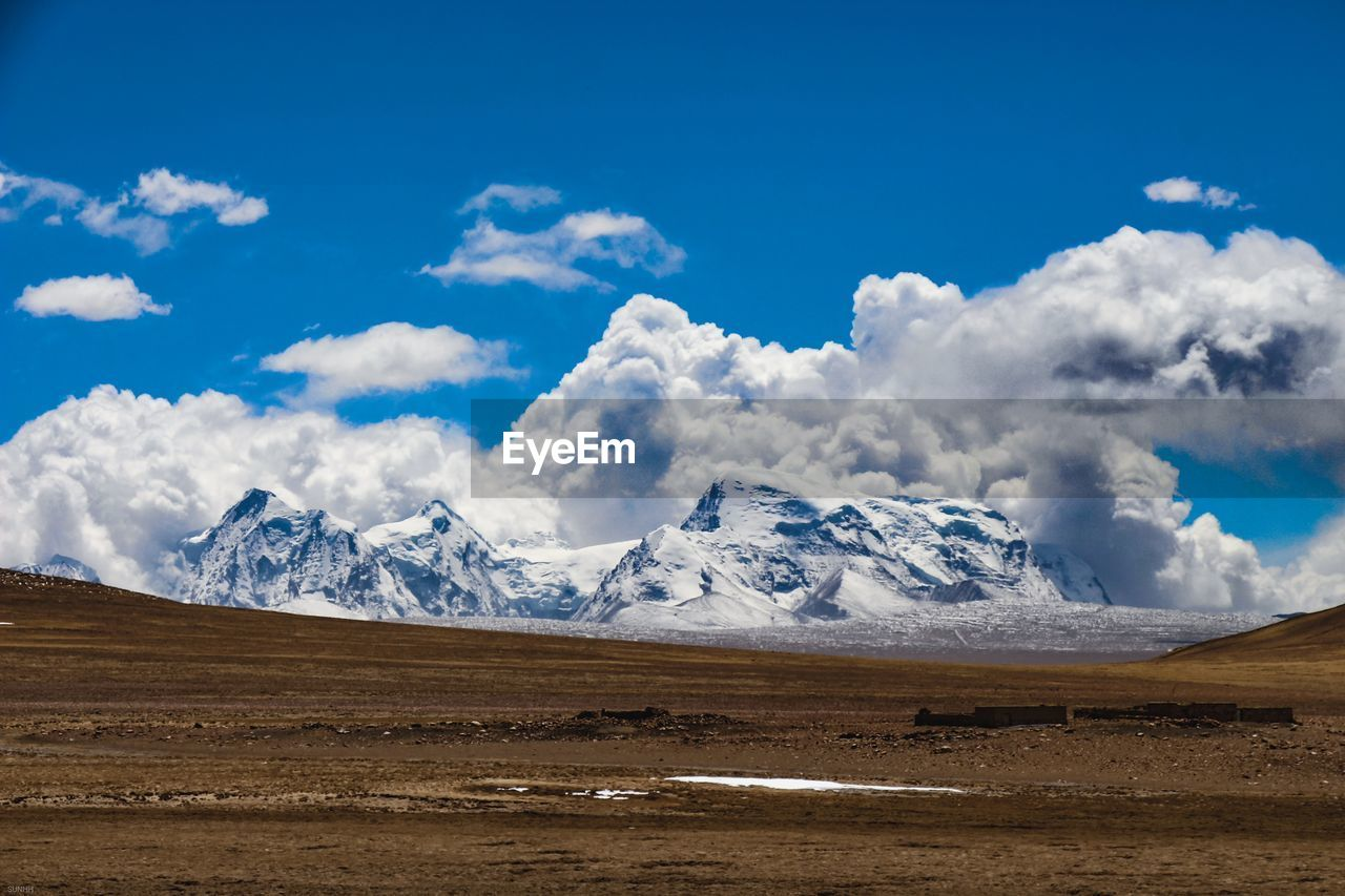 Scenic view of snowcapped mountains against blue sky