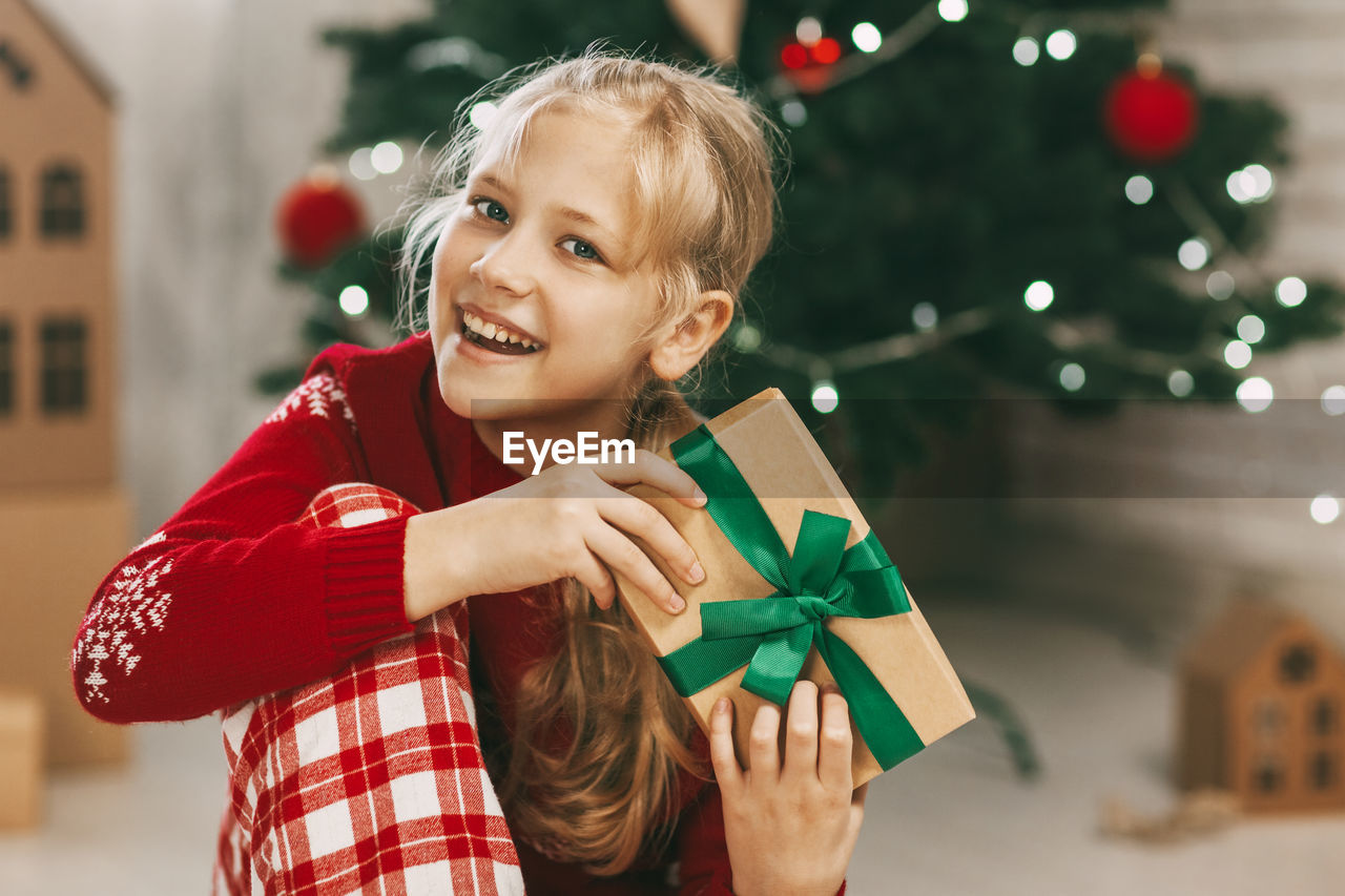 A beautiful little girl looks at the camera and smiles, holding a kraft paper gift