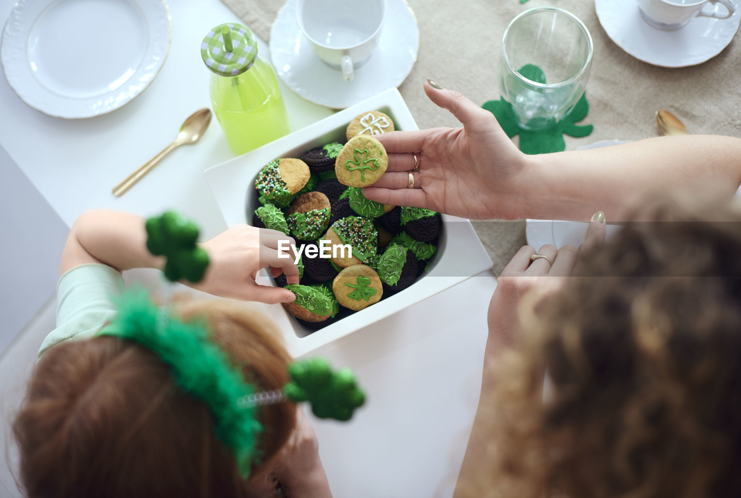 High angle view of mother with daughter making cookies on table