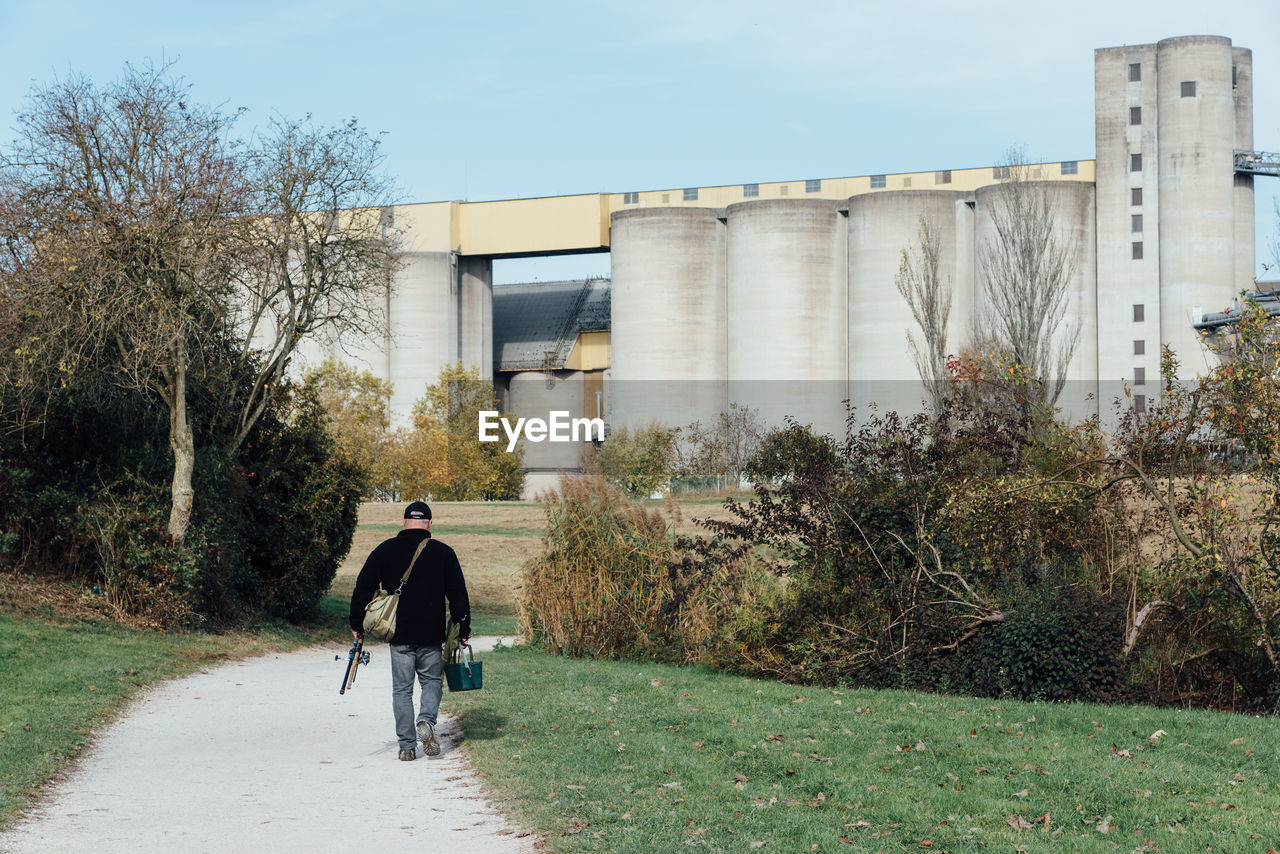 architecture, built structure, plant, full length, rear view, real people, tree, men, lifestyles, one person, walking, nature, transportation, day, building exterior, sky, outdoors, casual clothing, the way forward