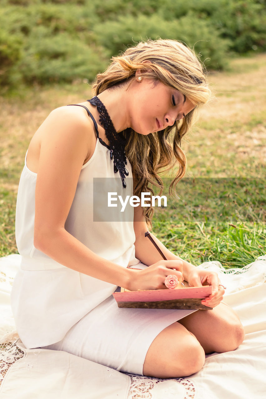 Young woman writing in book sitting outdoors