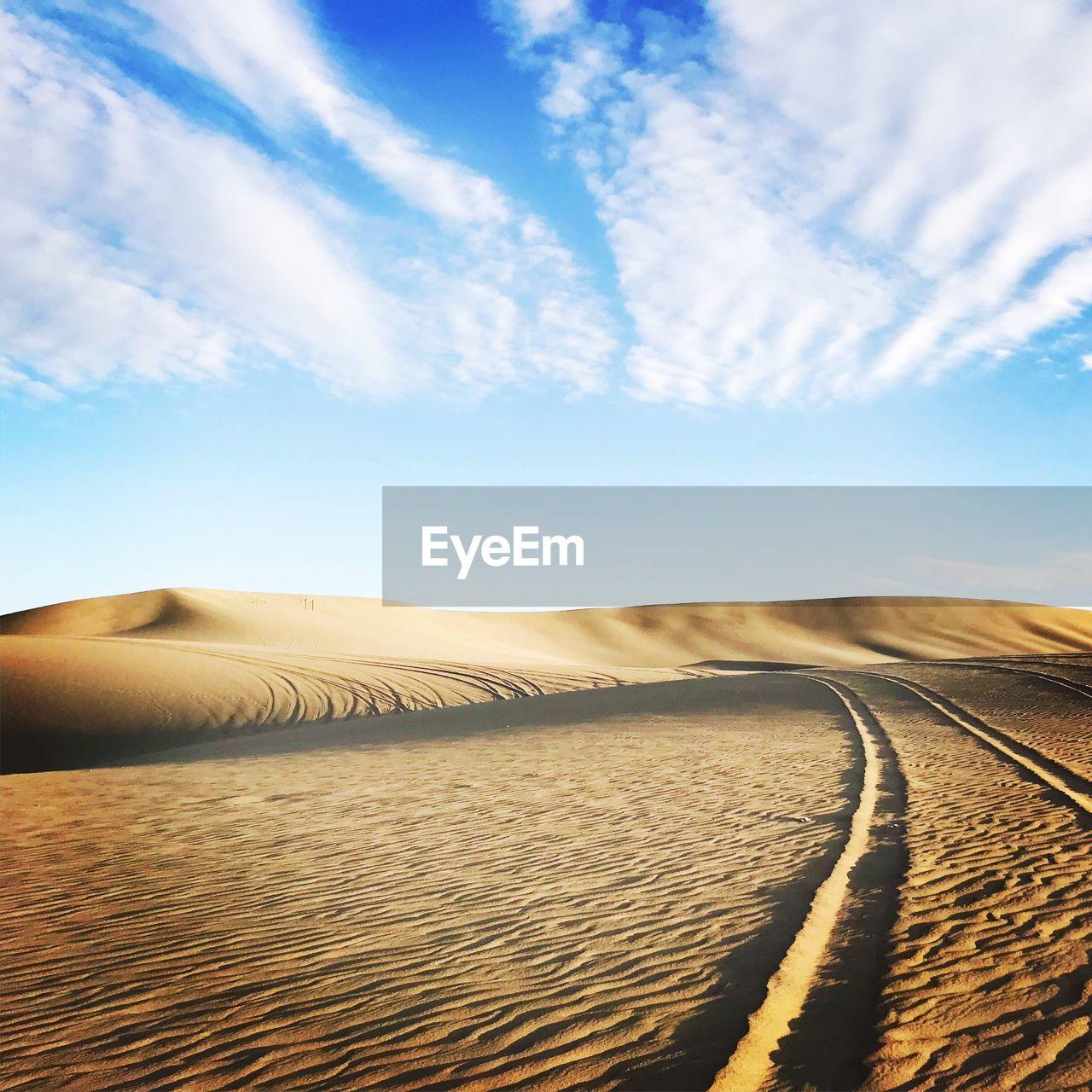 Scenic View Of Desert Against Blue Sky