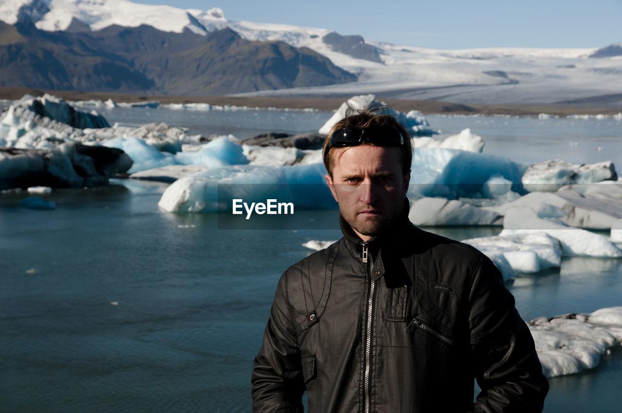 Portrait of man standing against frozen lagoon