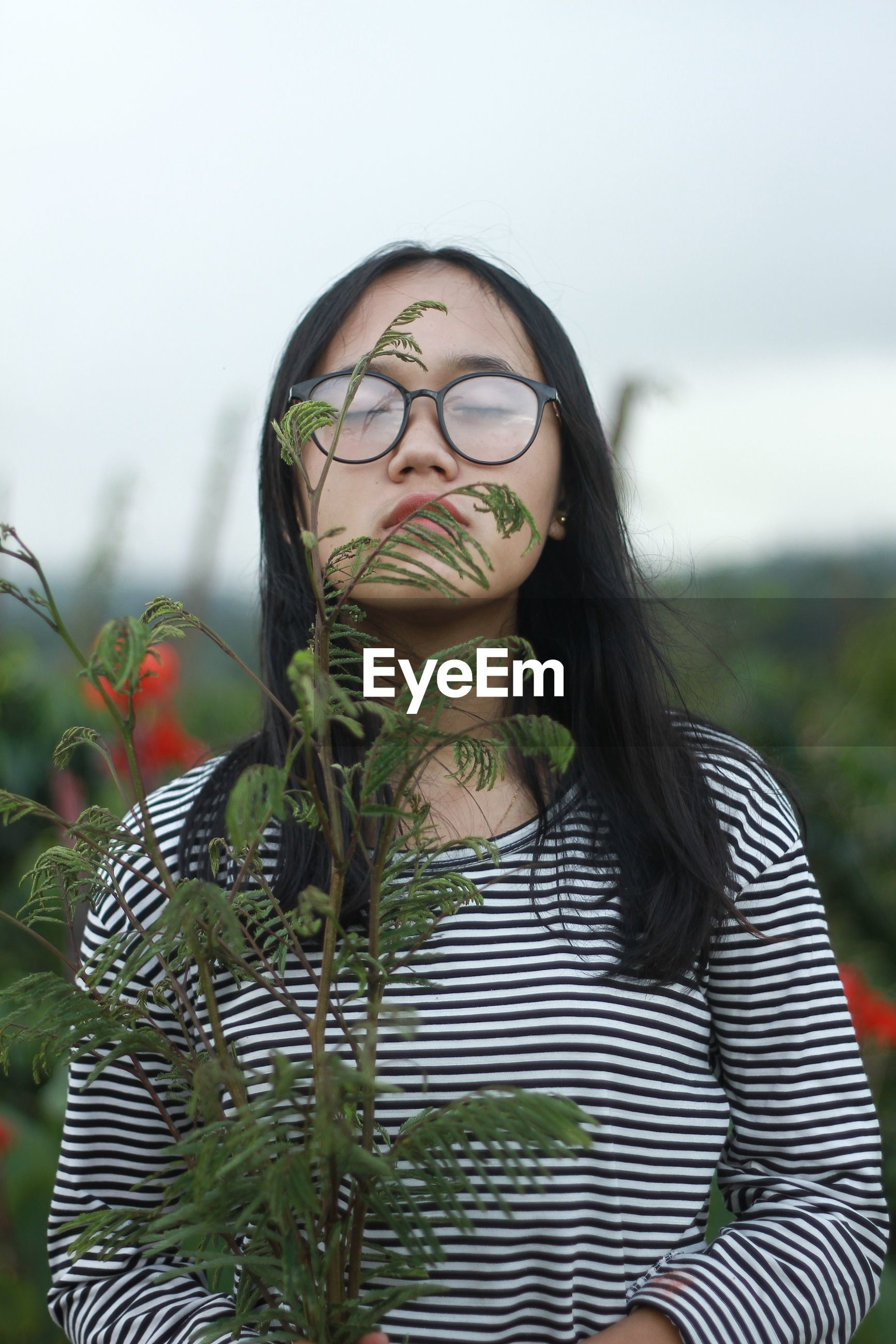 Young woman with eyes closed standing behind green leaves