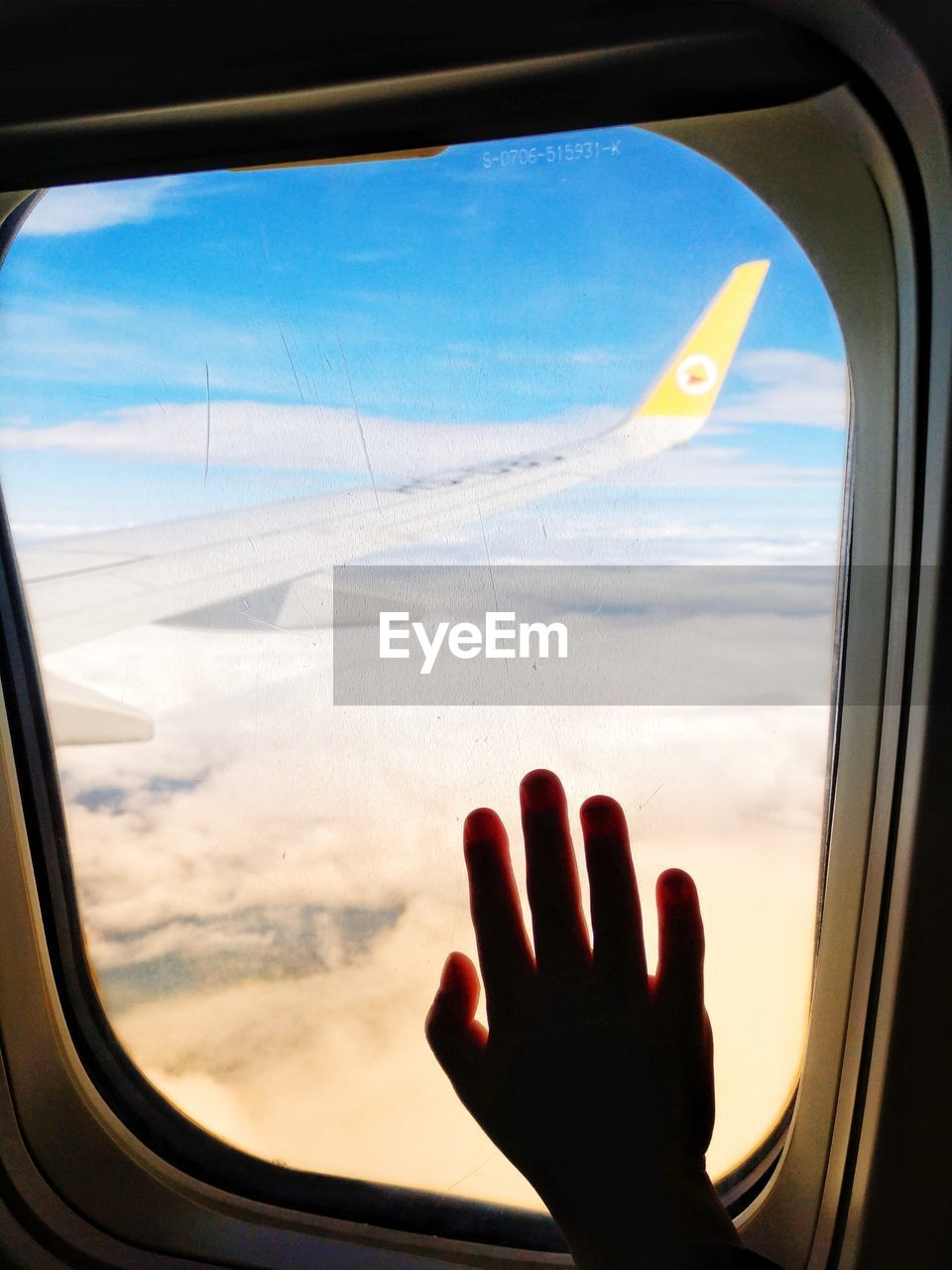 window, glass - material, air vehicle, sky, airplane, transportation, transparent, mode of transportation, cloud - sky, vehicle interior, one person, flying, nature, human hand, human body part, hand, mid-air, indoors, travel, finger