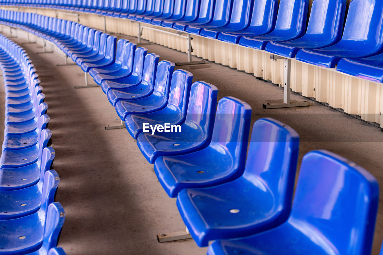 blue, in a row, seat, absence, empty, repetition, chair, side by side, order, no people, indoors, large group of objects, arrangement, sport, stadium, high angle view, plastic, abundance, still life, day, foldable