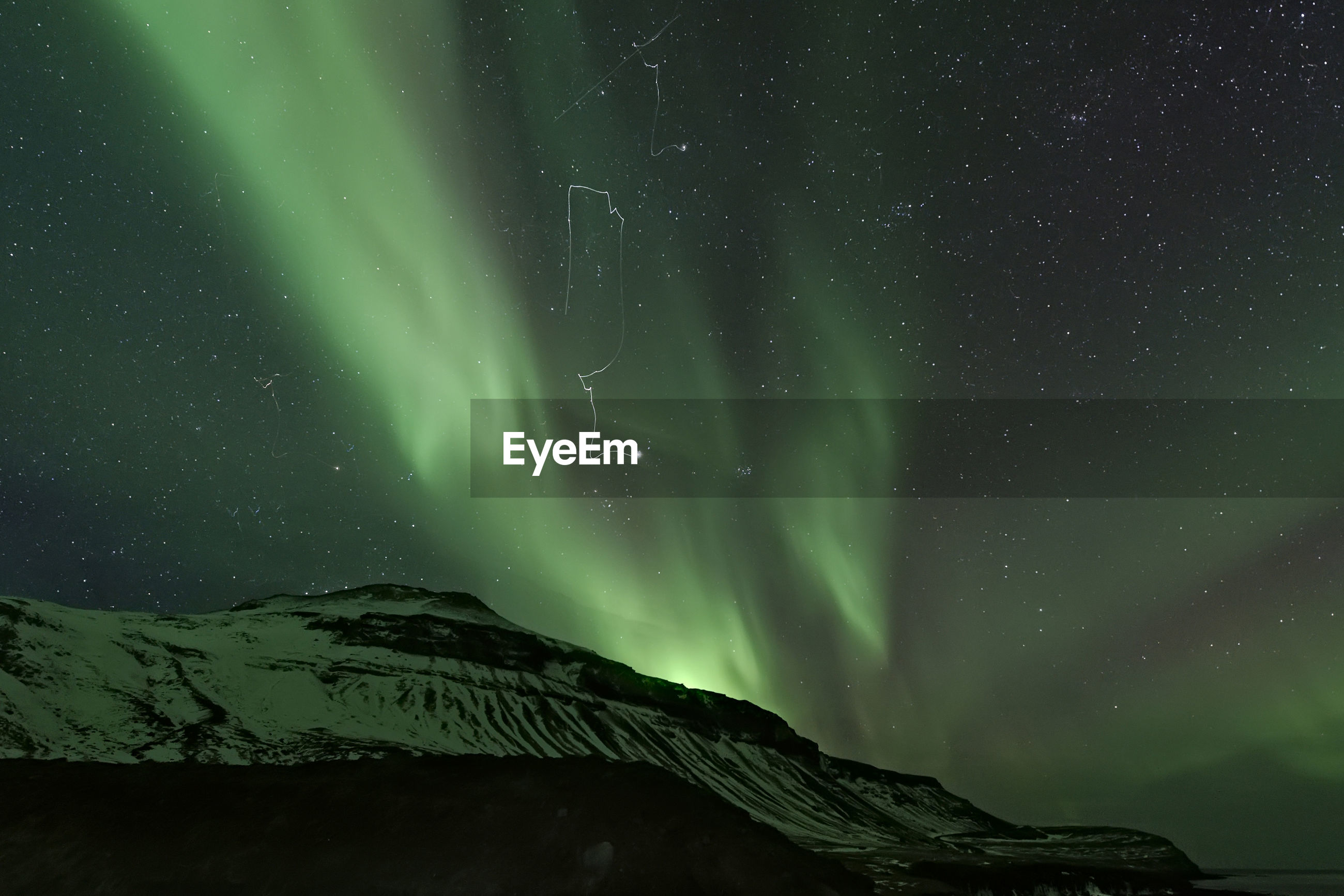 Low angle view of mountain against aurora borealis at night