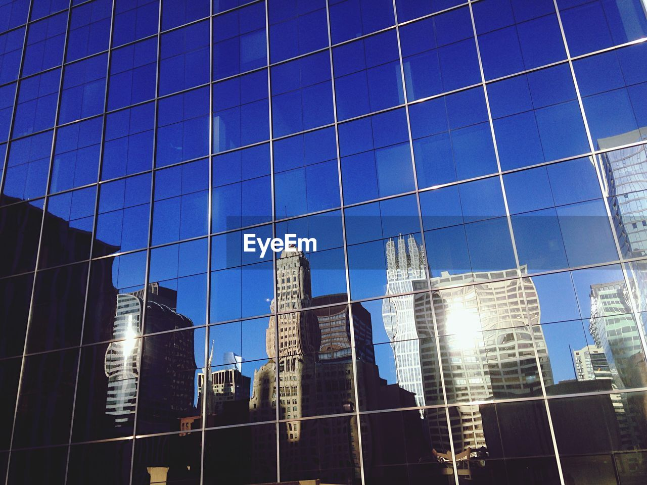 Low Angle View Of Buildings Reflecting On Glass Window