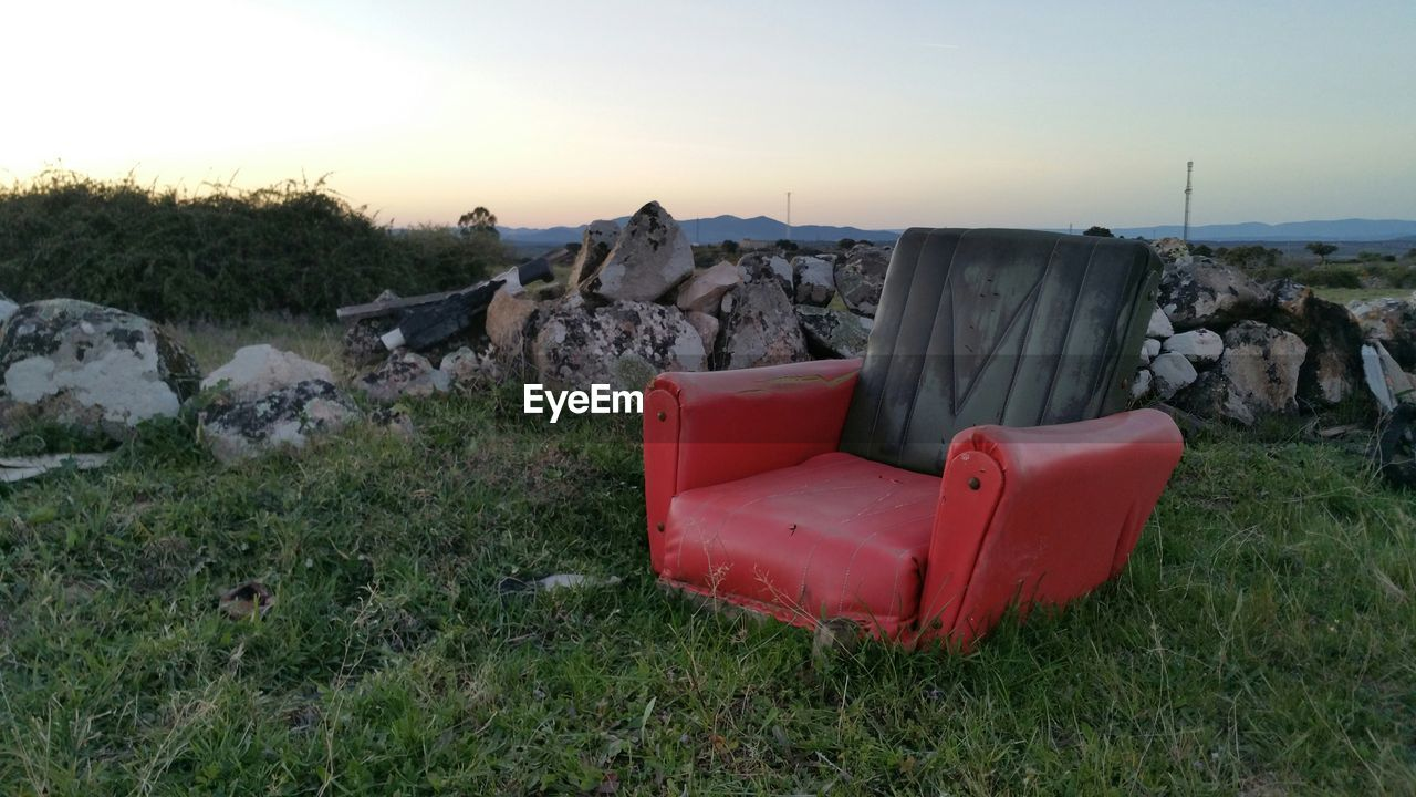 Abandoned empty armchair on field