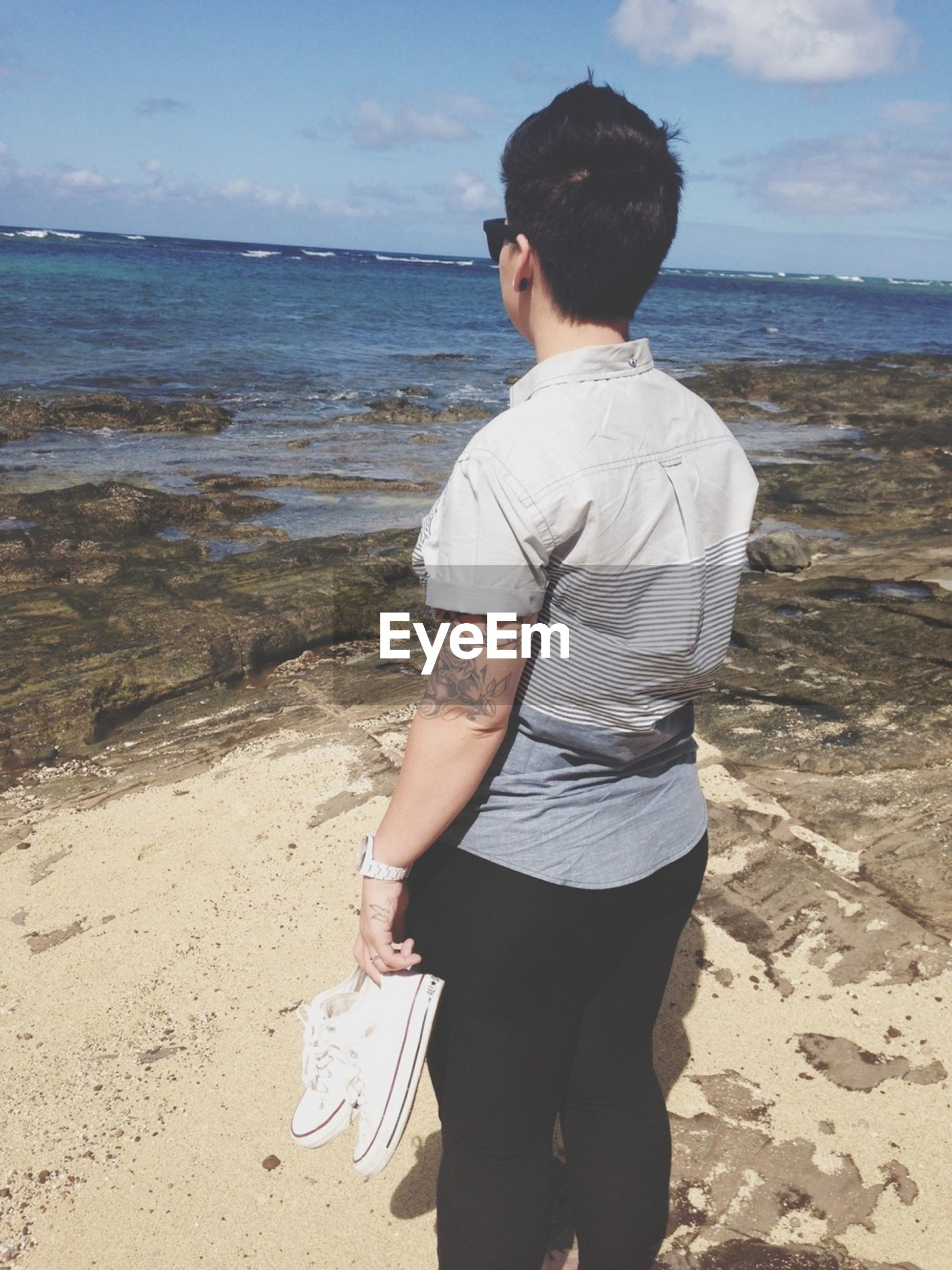 water, casual clothing, sea, lifestyles, standing, sky, beach, leisure activity, young adult, shore, full length, person, three quarter length, rear view, sunglasses, nature, horizon over water, outdoors