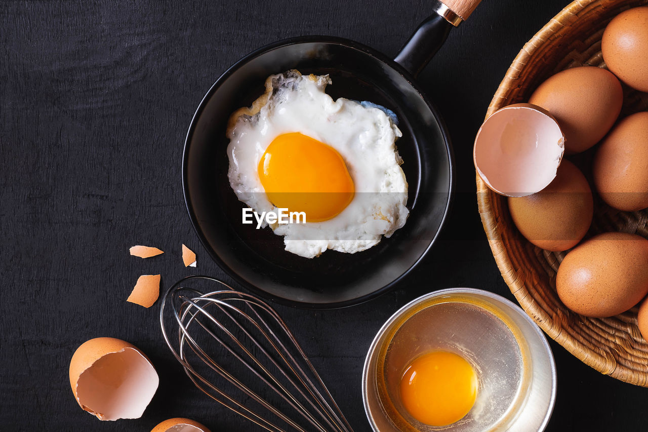 egg, food, food and drink, kitchen utensil, egg yolk, healthy eating, freshness, indoors, fried egg, wellbeing, preparation, fried, directly above, frying pan, household equipment, table, high angle view, ready-to-eat, wire whisk, preparing food, no people, meal, breakfast, sunny side up