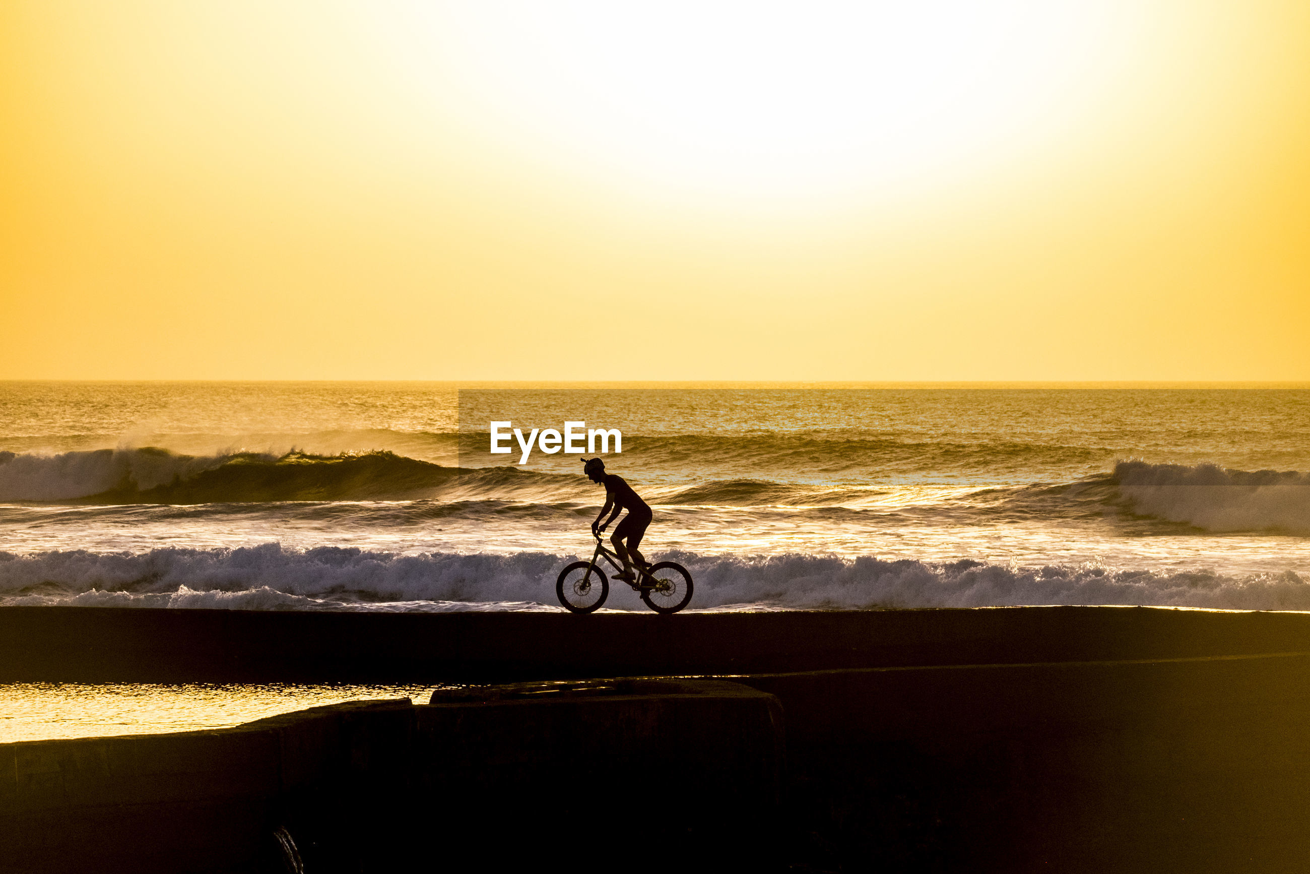 Silhouette man riding bicycle on shore at beach against clear sky during sunset