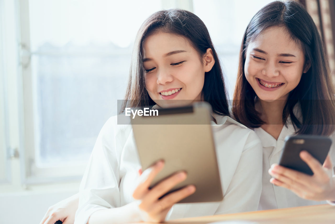 Smiling Business Colleagues Using Digital Tablet In Office
