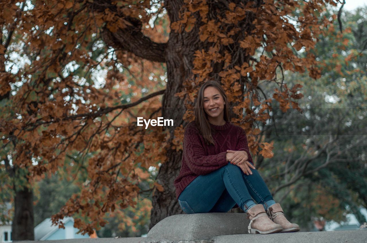 Portrait of smiling young woman sitting under tree outdoors