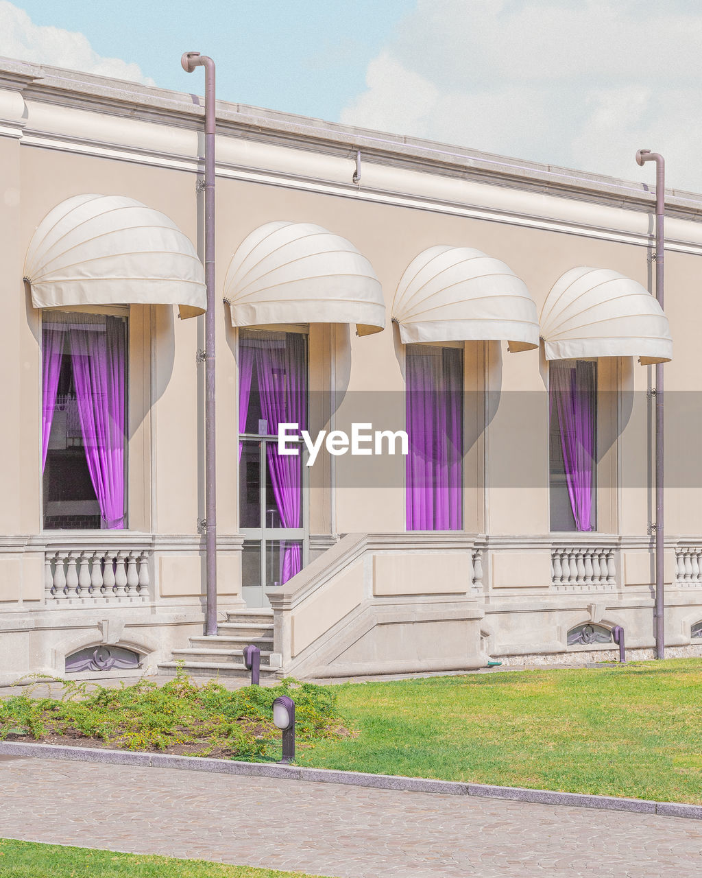 architecture, building exterior, built structure, sky, no people, day, nature, building, purple, outdoors, grass, side by side, plant, city, glass - material, railing, window, architectural column, in a row, sunlight, luxury