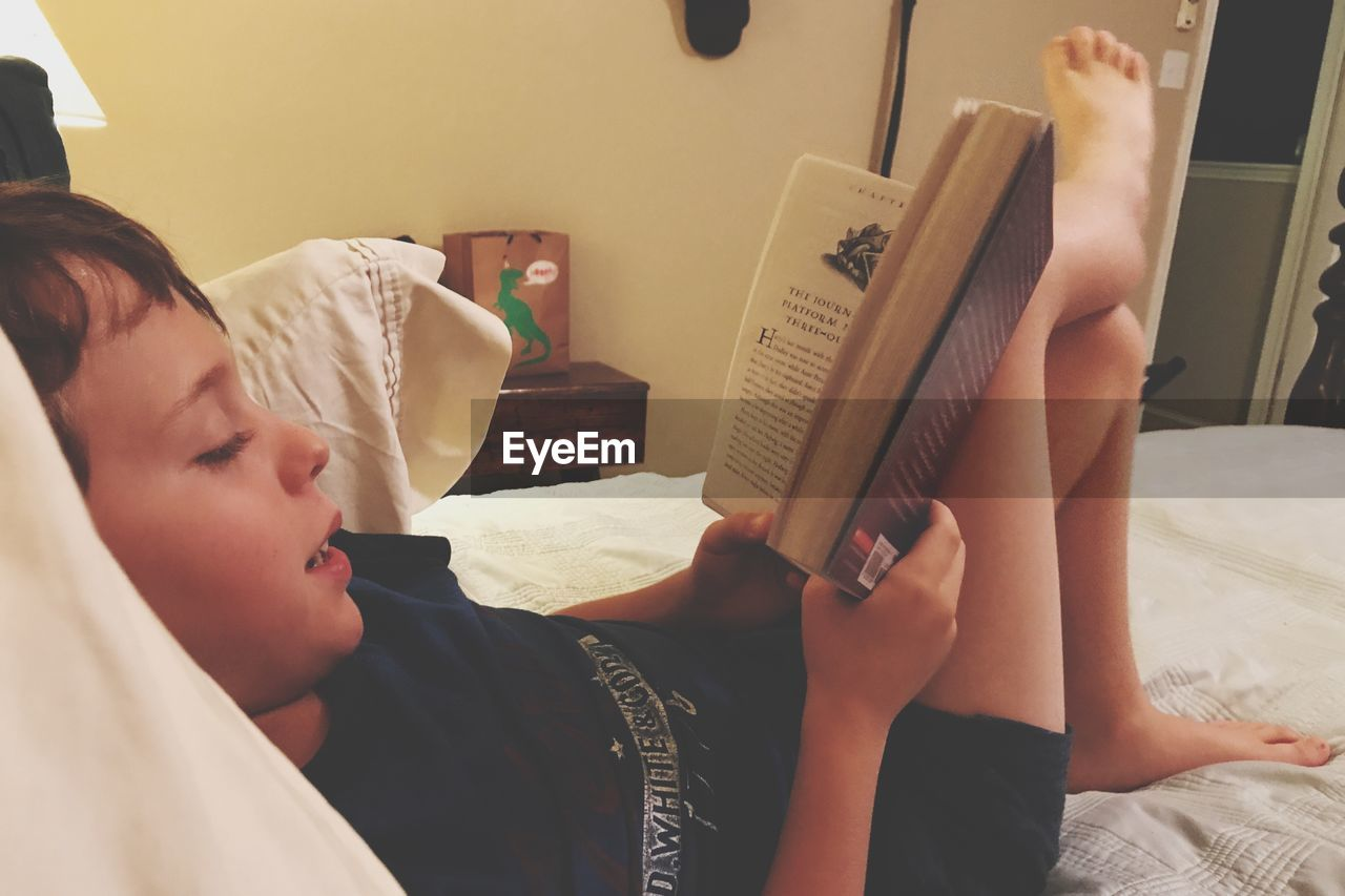 bed, book, education, indoors, learning, bedroom, one person, real people, holding, sitting, boys, childhood, paper, human hand, young adult, close-up, day, people