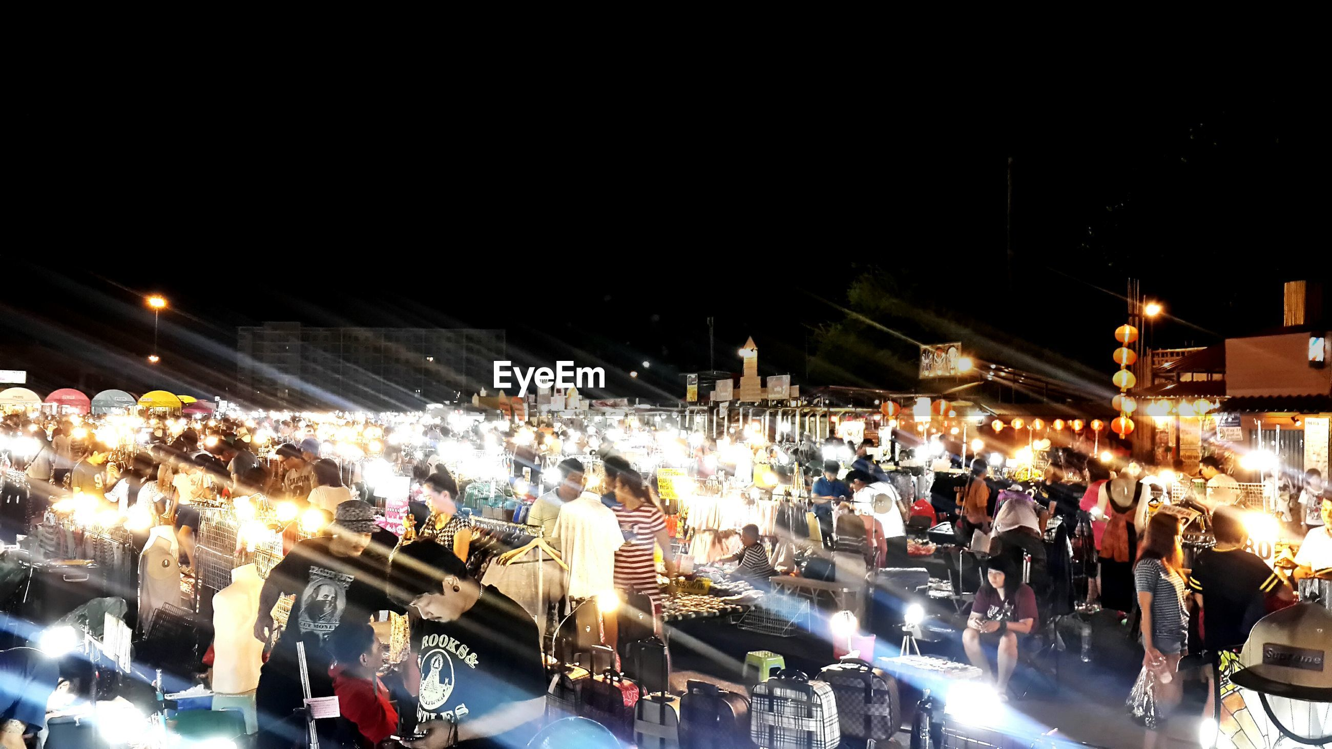 People in illuminated market against sky at night