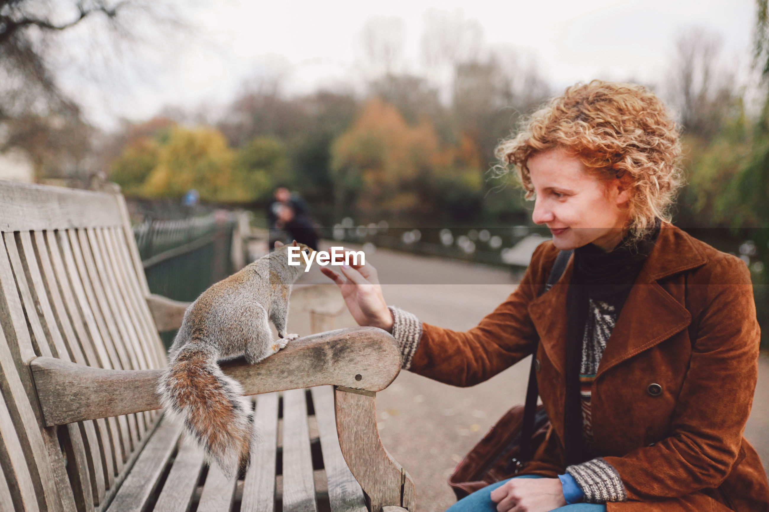 Smiling woman playing with squirrel on bench in park
