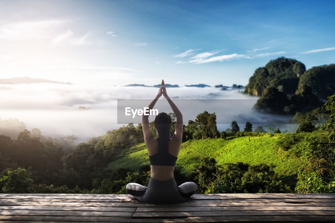 Rear view of woman practicing yoga while sitting on floorboard in nature