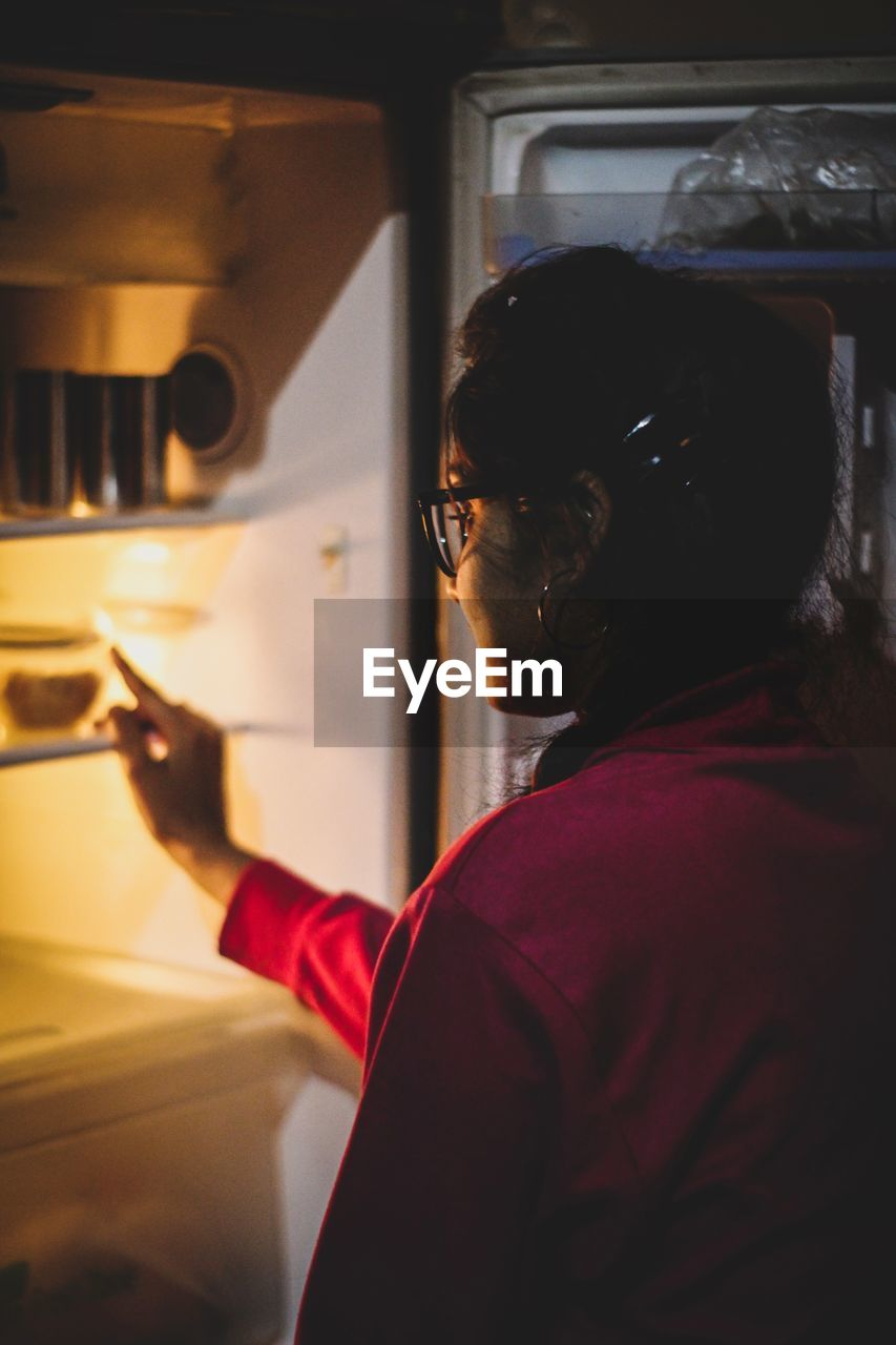 Woman standing by fridge at home