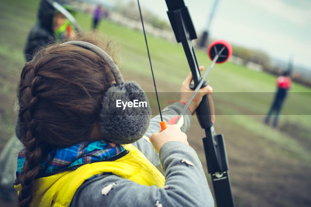 Rear View Of Girl Practicing Archery