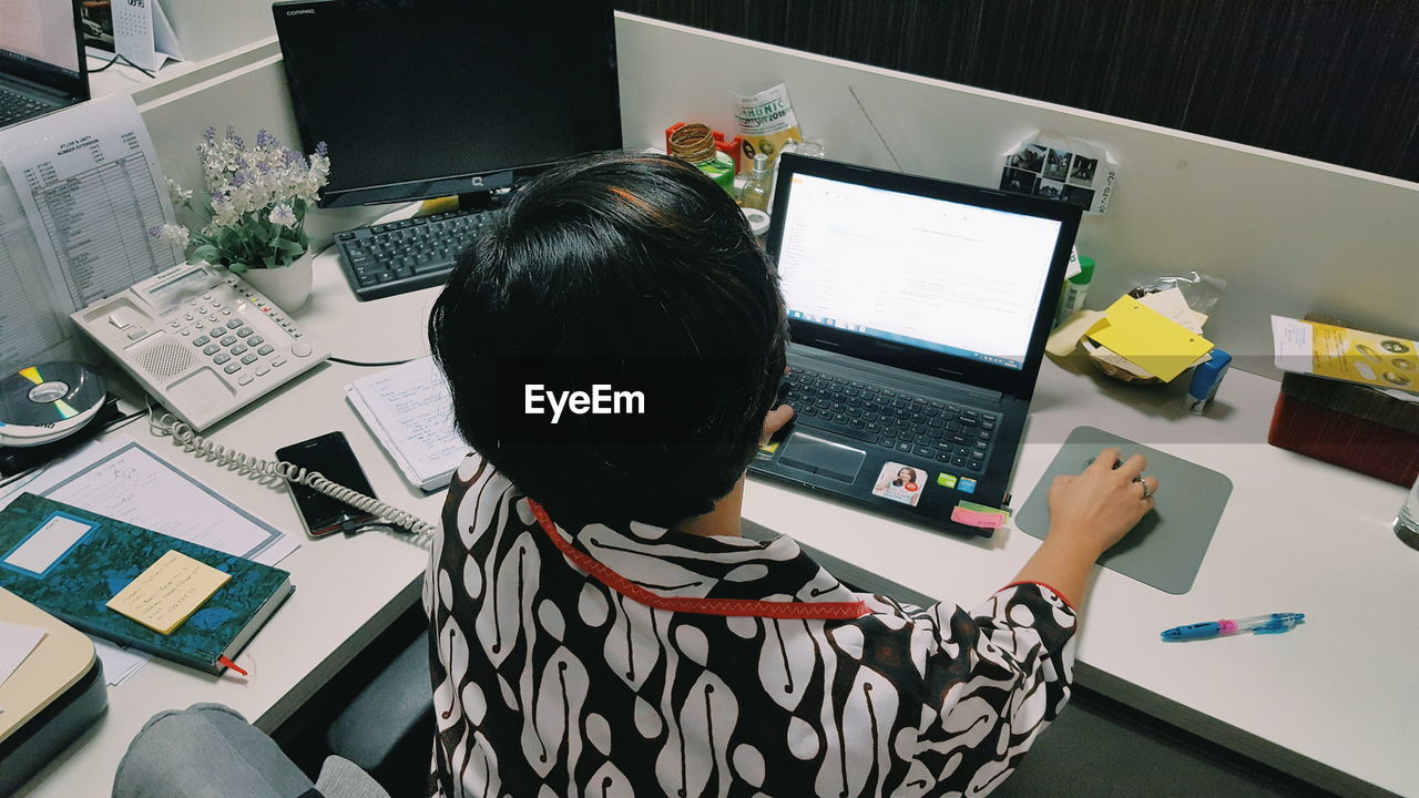 Rear view of businesswoman working with laptop at office