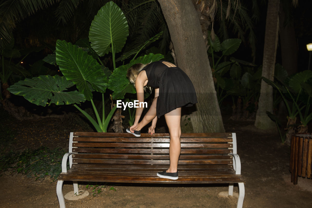 Young Woman Tying Shoes On Bench At Night