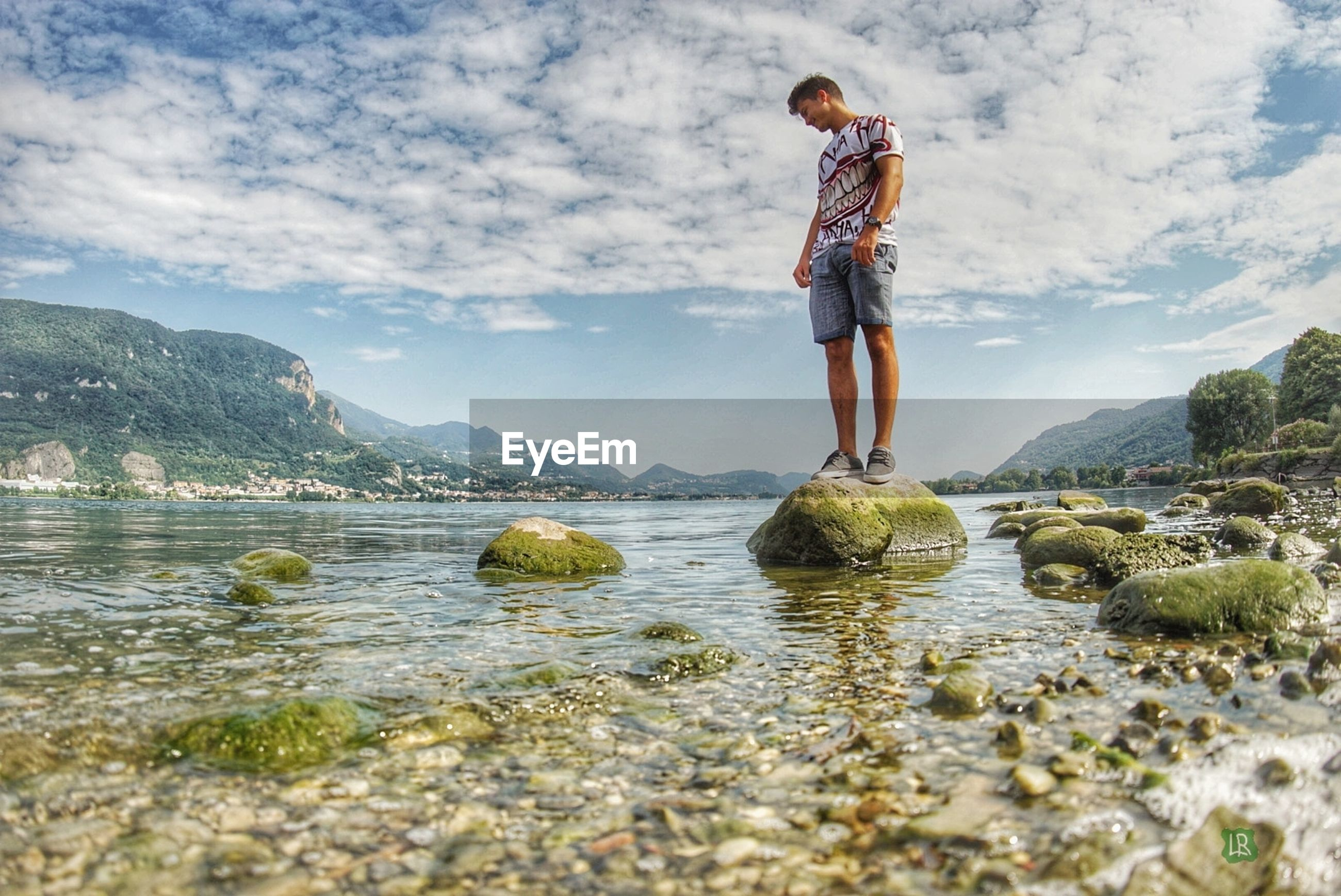 one person, lifestyles, water, real people, beauty in nature, full length, scenics - nature, mountain, leisure activity, sky, rock, solid, day, casual clothing, cloud - sky, rock - object, nature, rear view, outdoors, looking at view