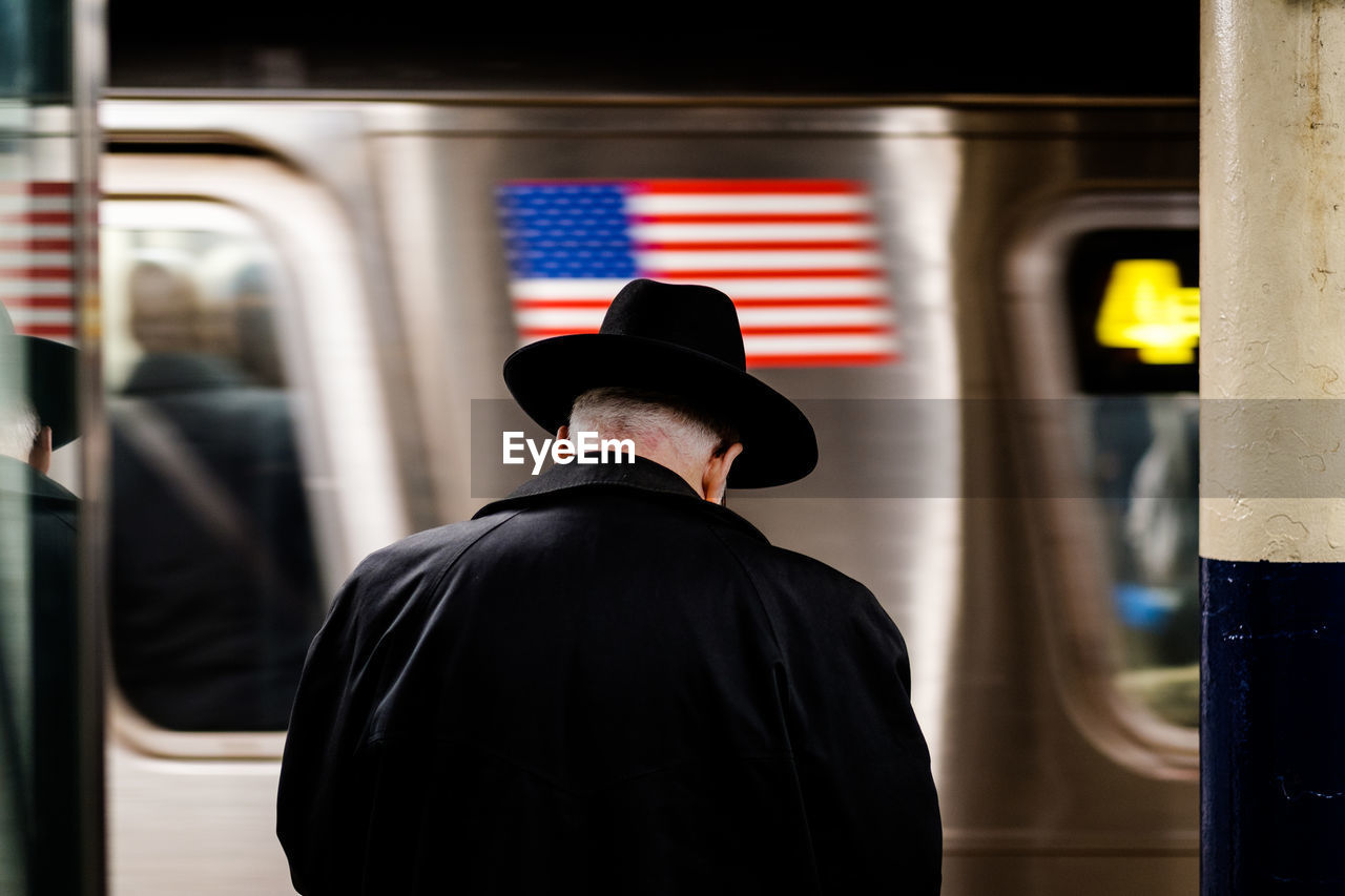 Rear view of man wearing hat against train at subway station