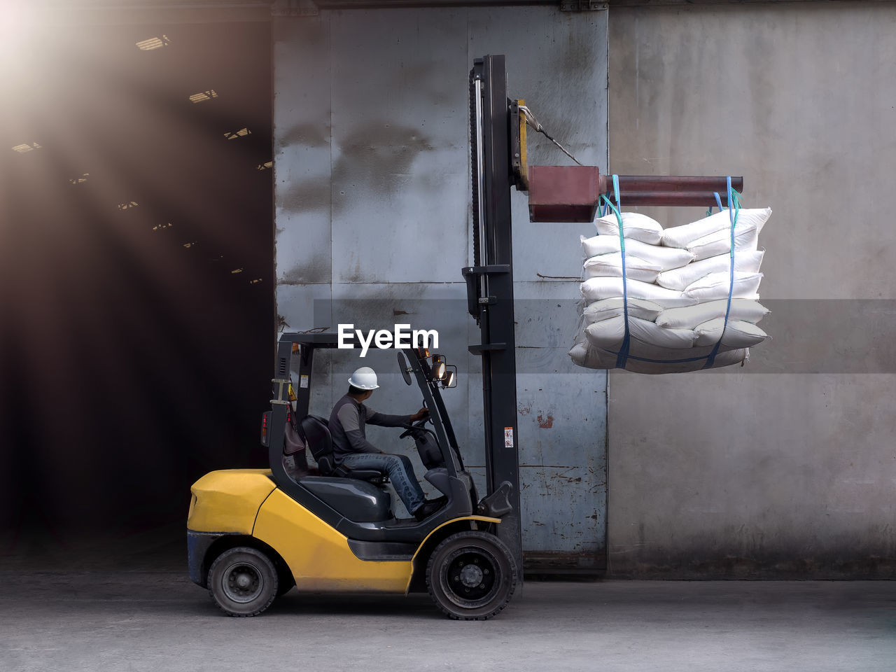 Manual Worker Driving Forklift While Working At Warehouse