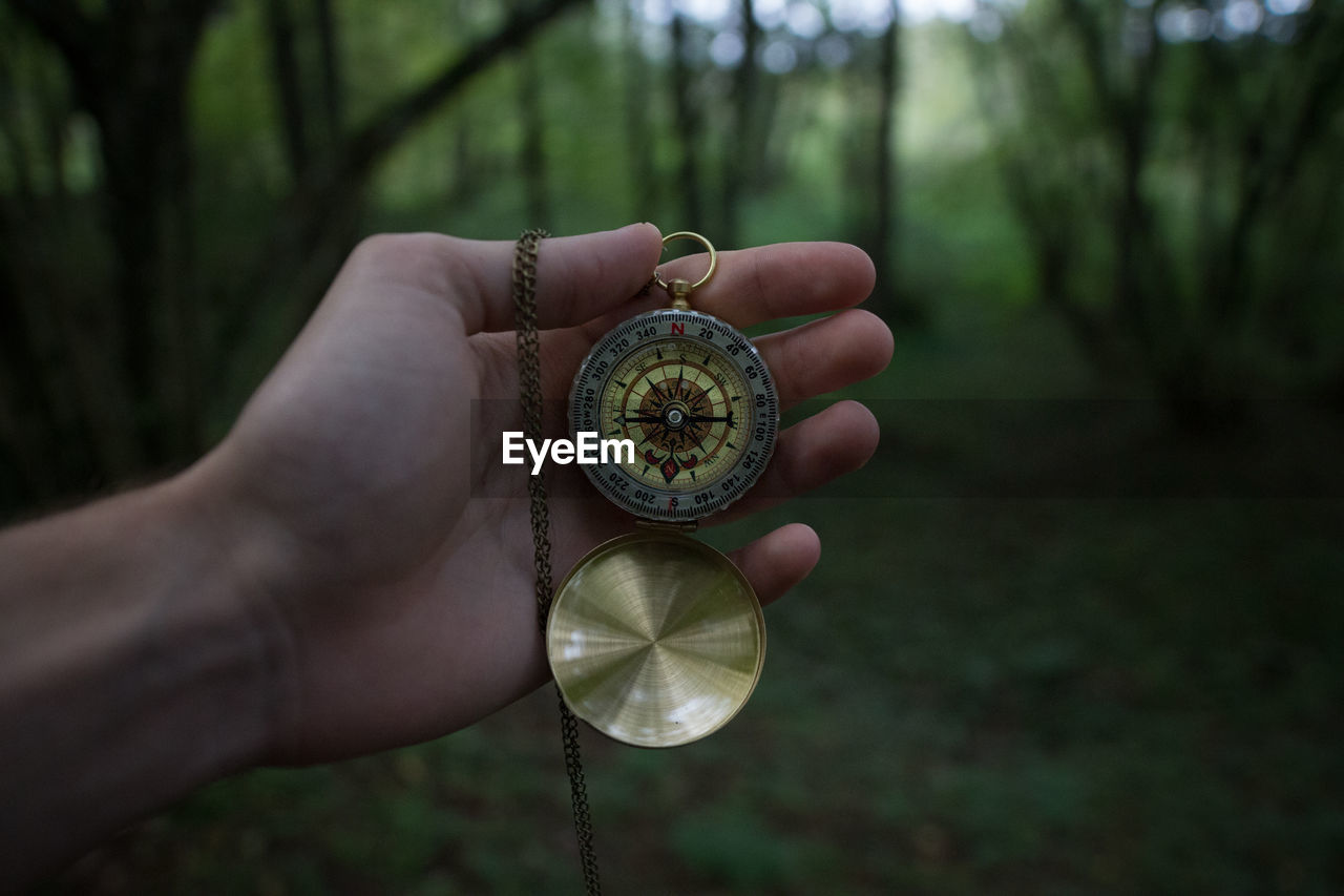 Cropped image of hand holding navigational compass in forest