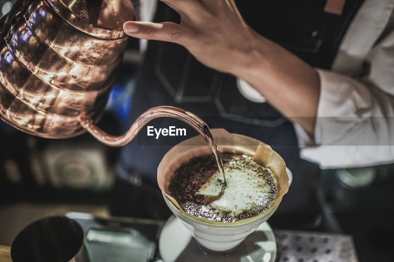 Close-Up Of Man Pouring Coffee In Cup