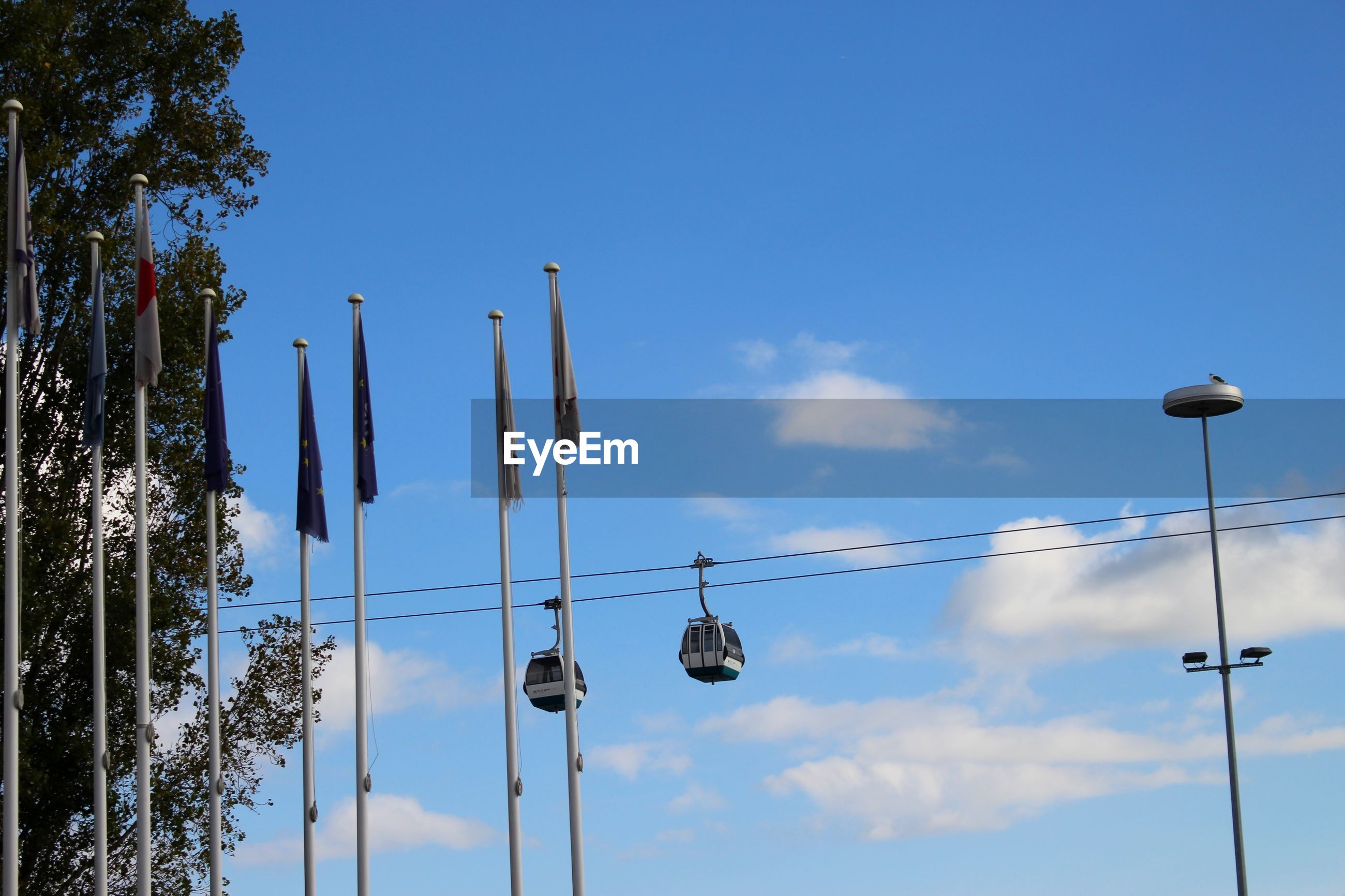 Low angle view of flags and cable cars against sky