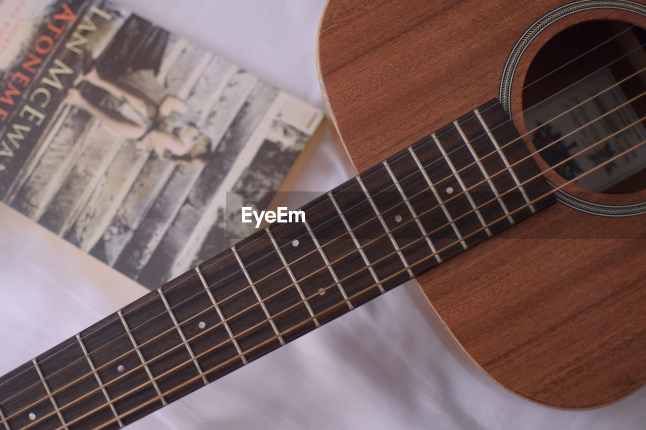 music, string instrument, musical instrument, arts culture and entertainment, musical equipment, guitar, string, musical instrument string, close-up, wood - material, indoors, still life, no people, acoustic guitar, fretboard, sheet music, focus on foreground, sheet, paper, brown