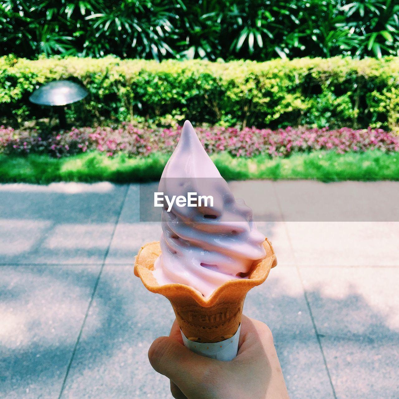 Cropped image of hand holding strawberry ice cream on sidewalk