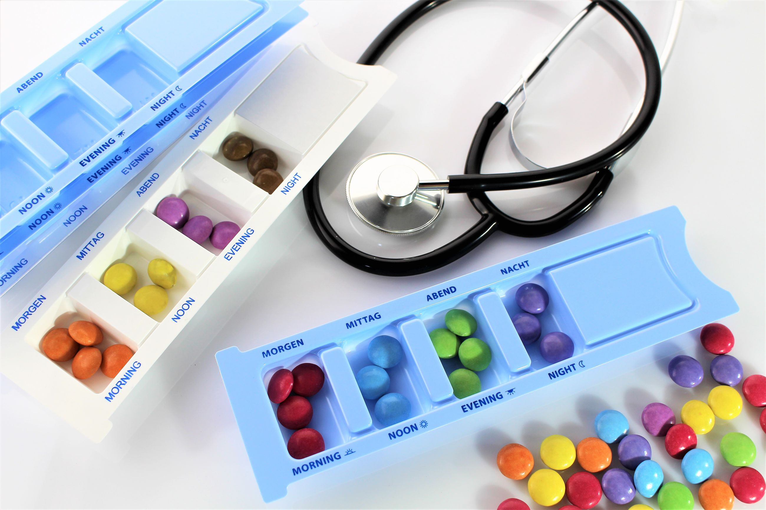 Close-up high angle view of medicines and stethoscope on white background
