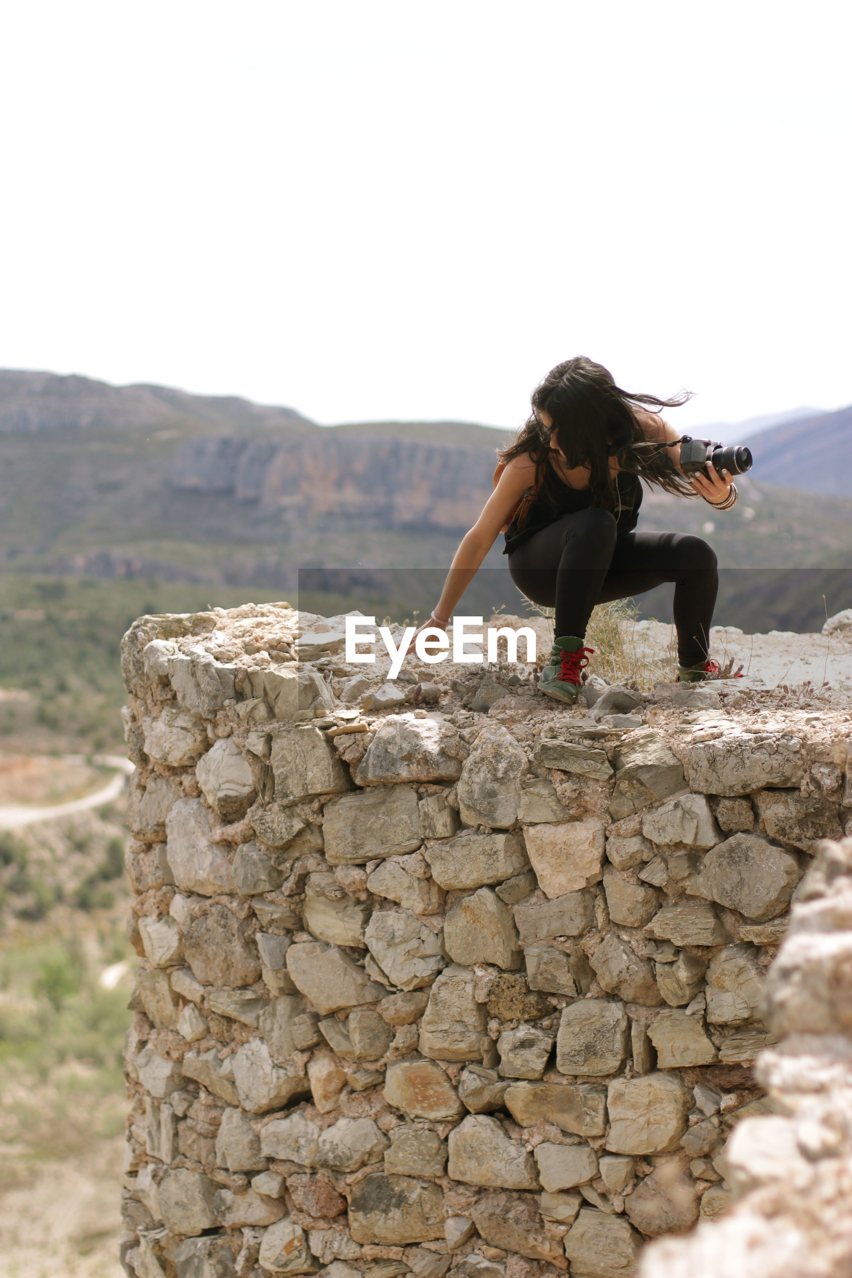 Woman holding camera while crouching on stone wall