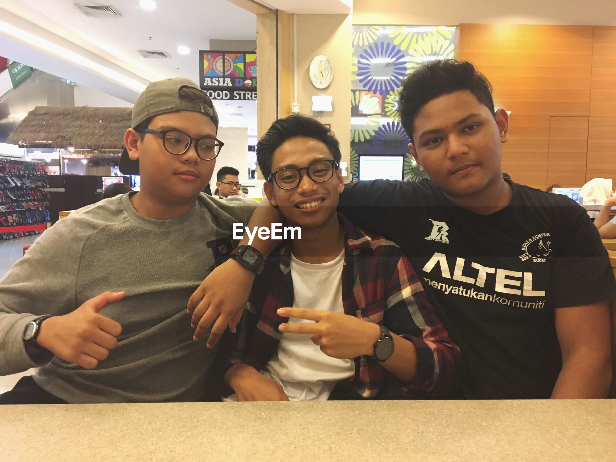 front view, real people, eyeglasses, standing, indoors, young men, young adult, food and drink, food, lifestyles, sitting, togetherness, men, day, friendship, people