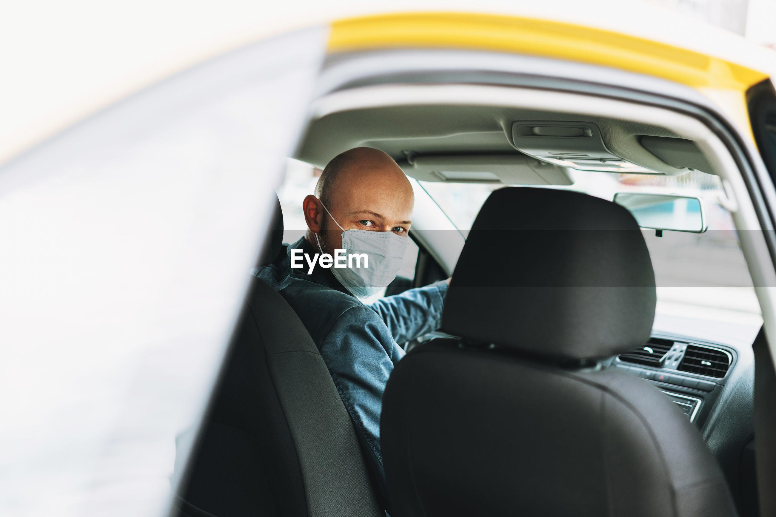 Portrait of man wearing mask sitting in car seen through window