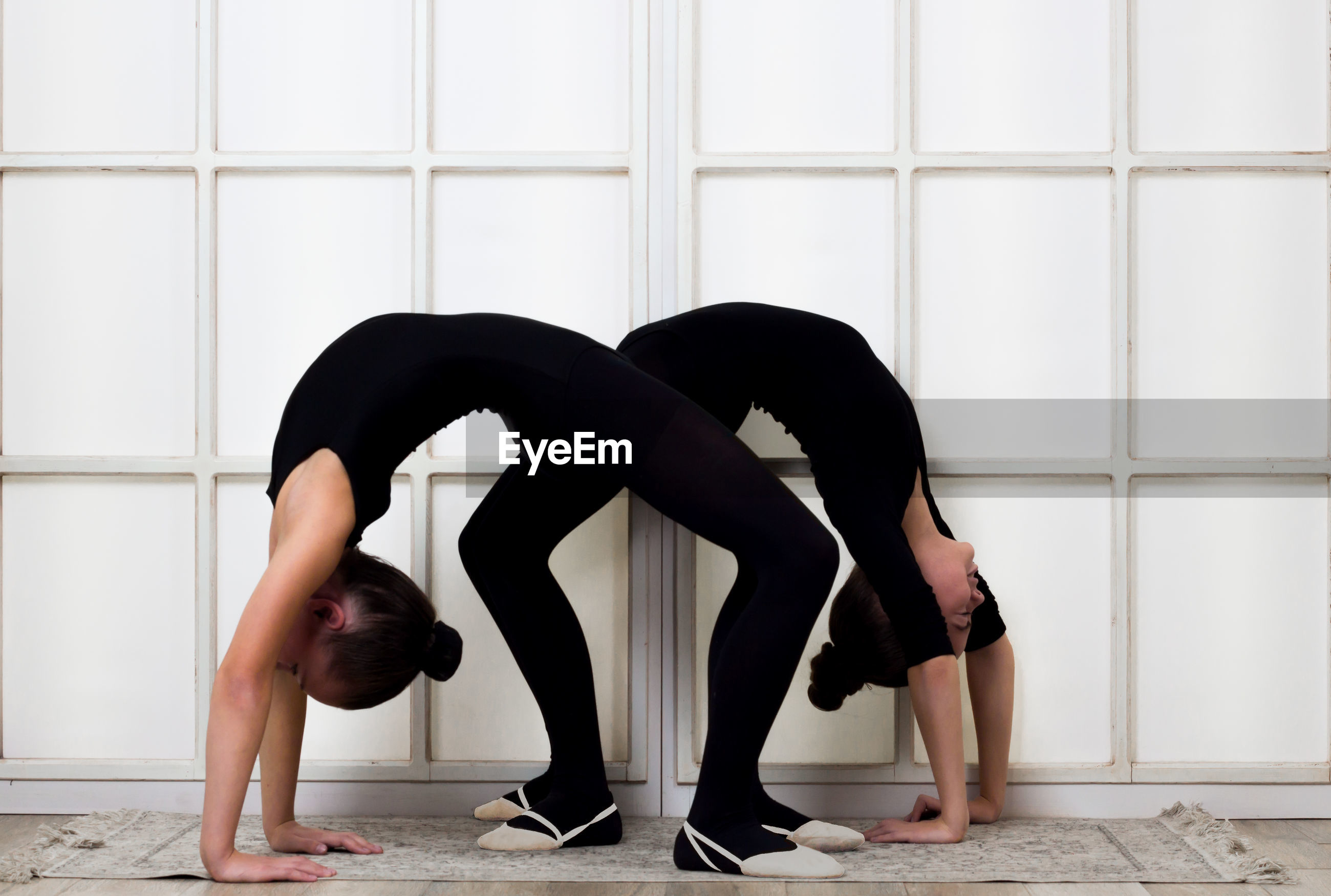 Side view of females bending over backwards