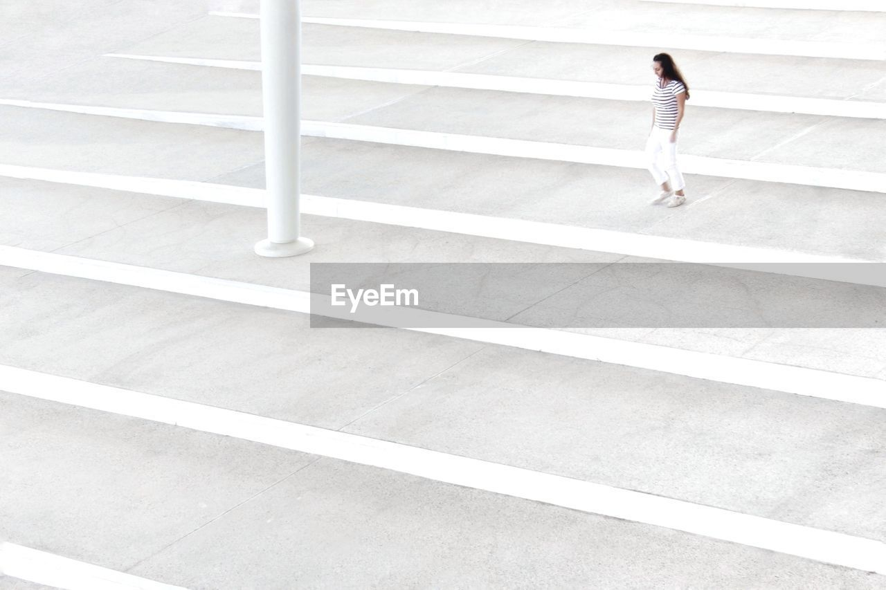 High angle view of woman walking on staircase