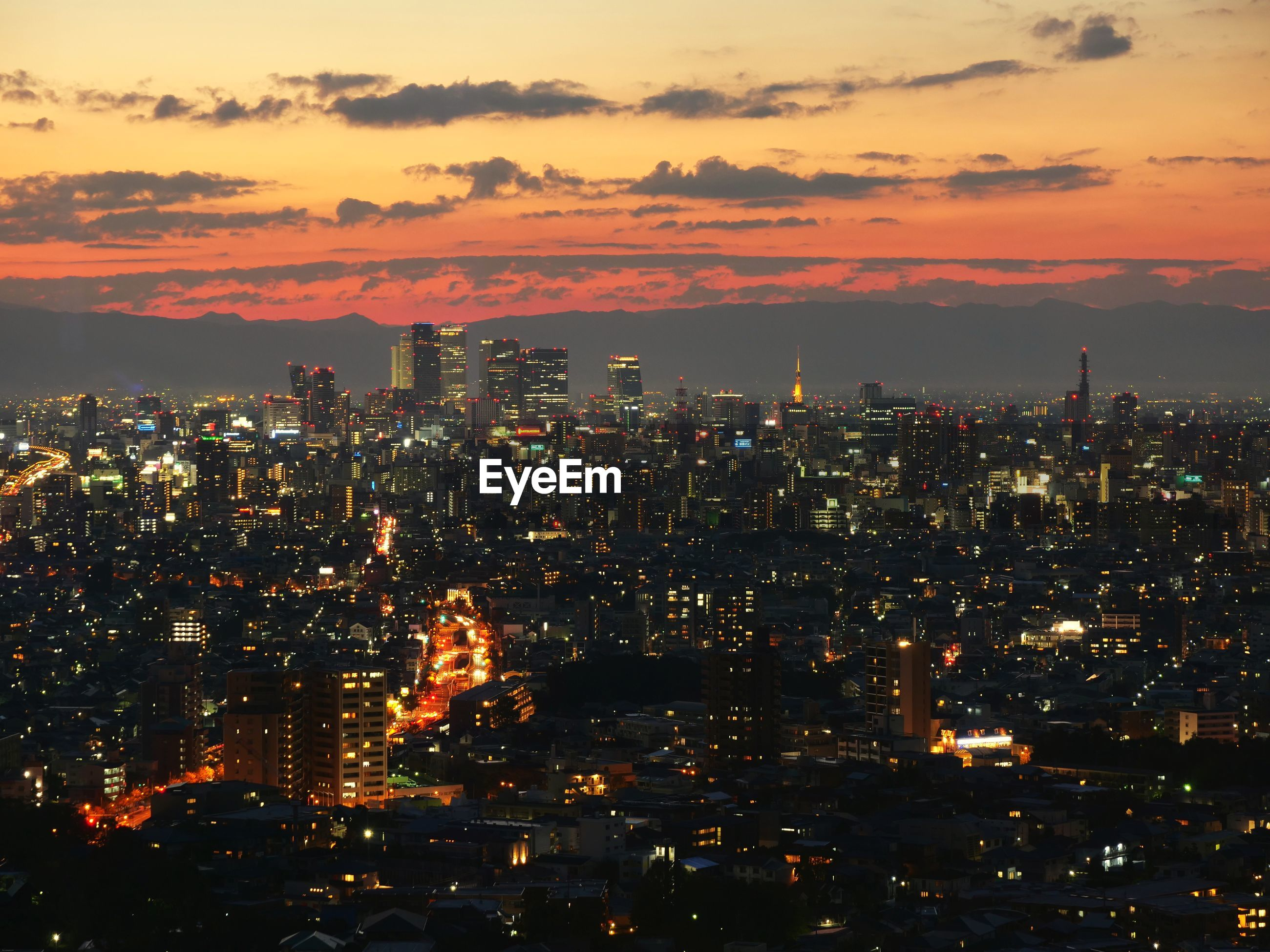HIGH ANGLE VIEW OF ILLUMINATED CITYSCAPE AGAINST SKY AT SUNSET