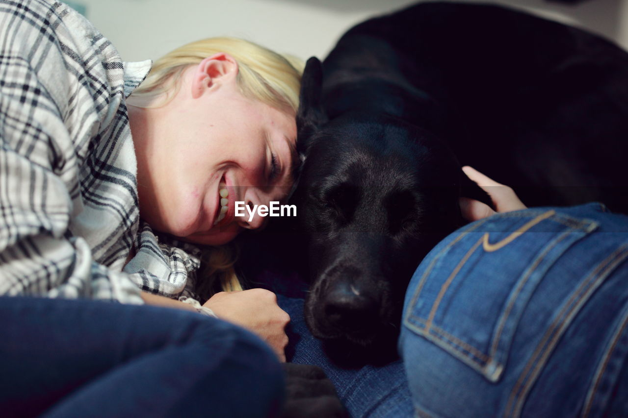 Young woman smiling while lying by black labrador on bed