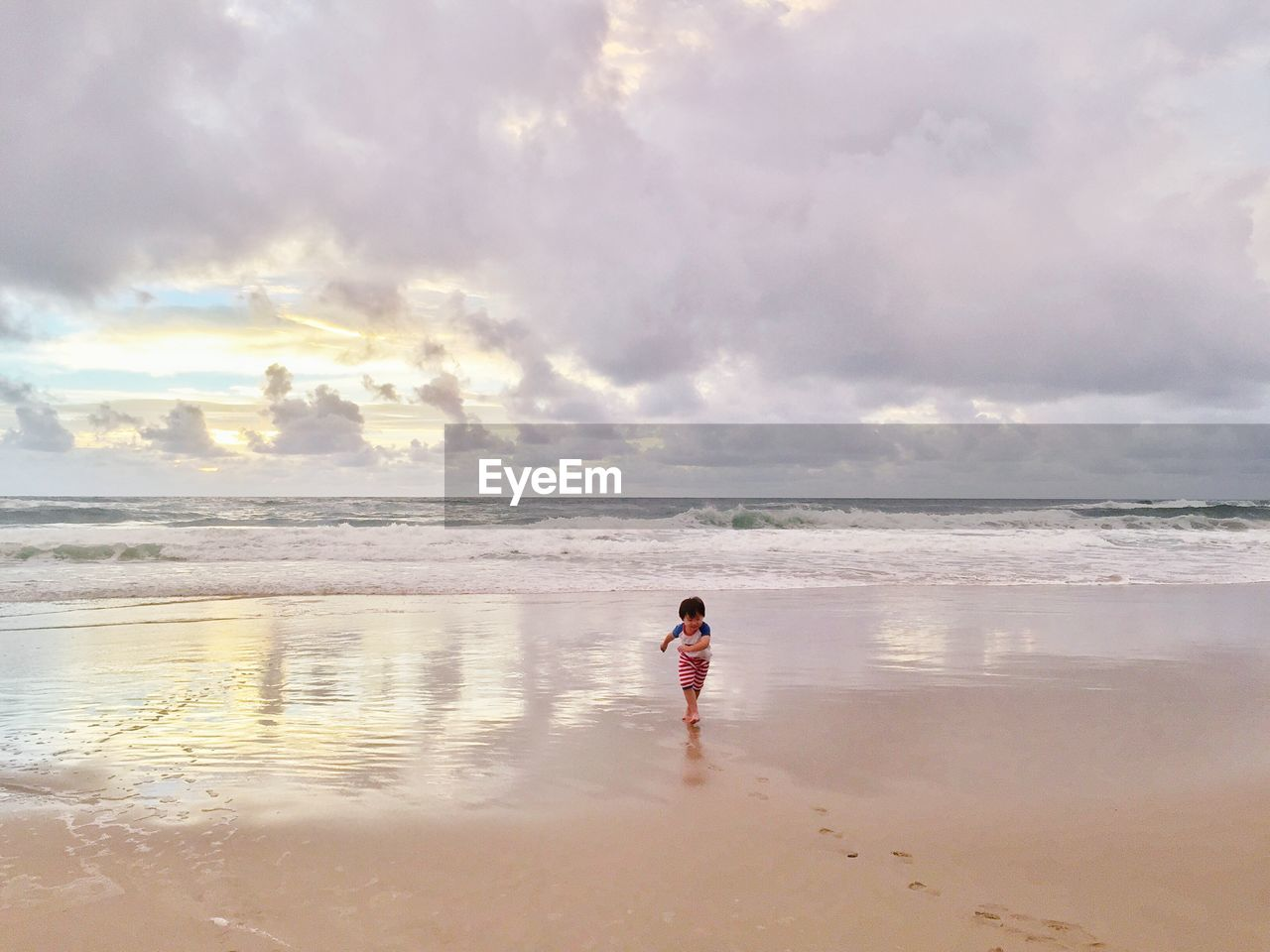 Toddler Running On Shore At Beach Against Cloudy Sky